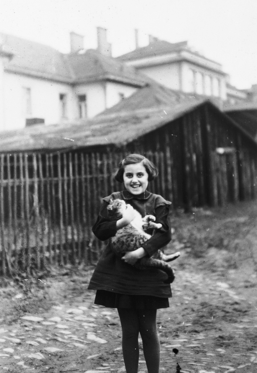 Kitty Weichherz stands by a fence holding a cat [perhaps in Cadca].  This photo was taken from the diary of Kitty's life written by her father, Bela Weichherz.