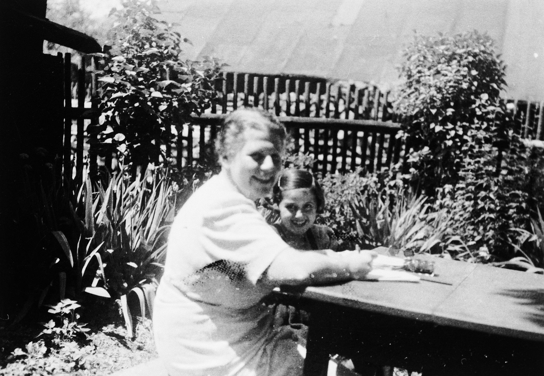 Kitty Weichherz sits with an older woman [possibly her grandmother] by a table in a garden.  This photo was taken from the diary of Kitty's life written by her father, Bela Weichherz.