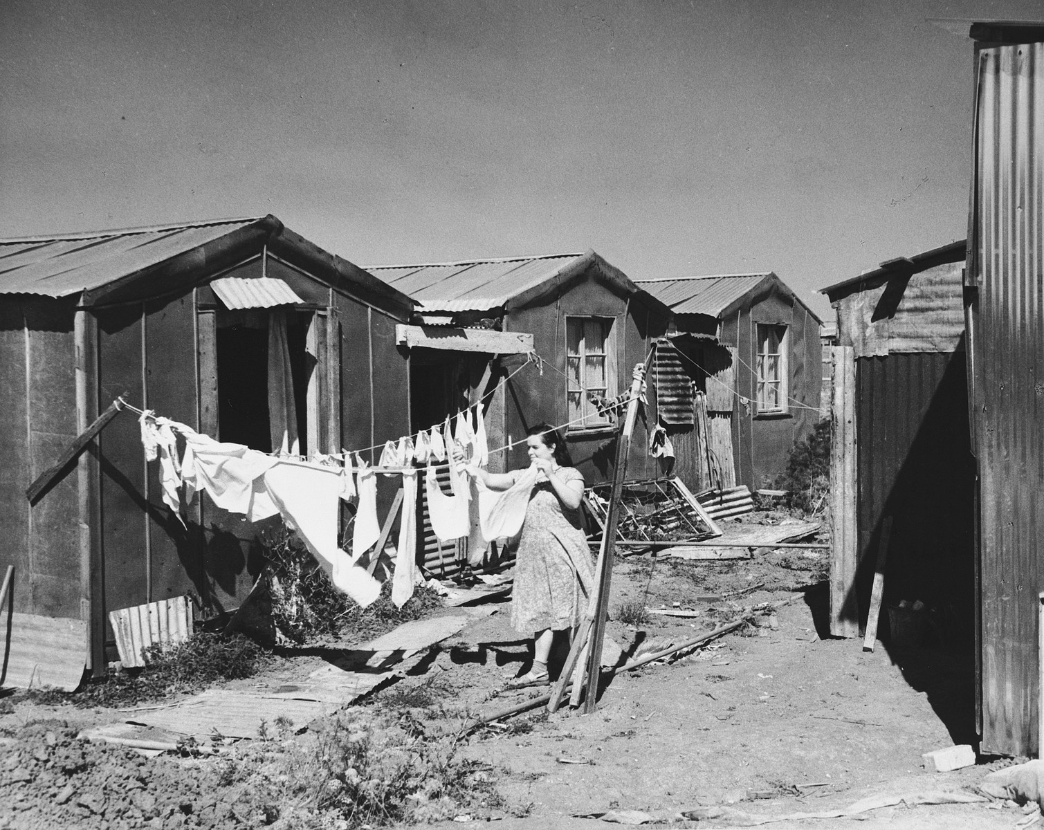 A new immigrant hangs her laundry outside a prefabricated shack in Tel Shachar.