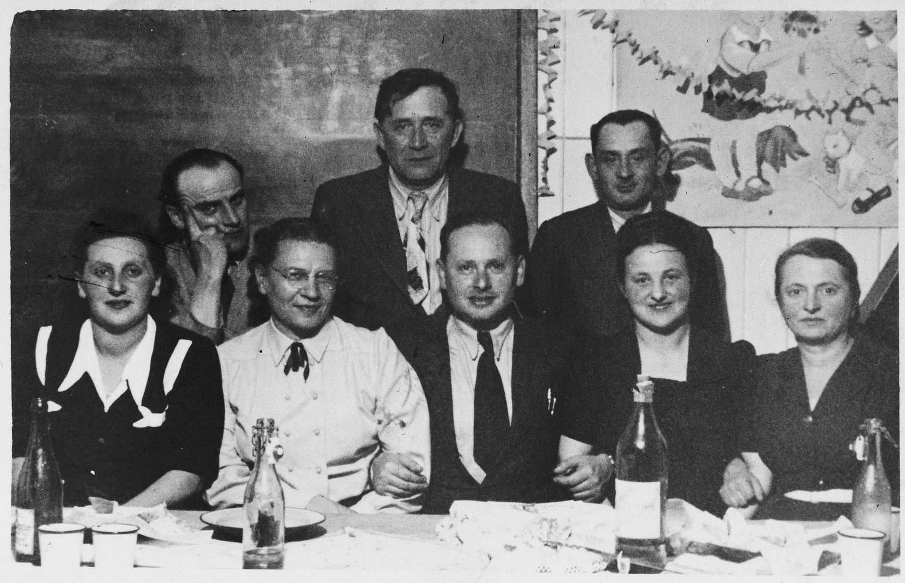 Administrators of the Wels dsiplaced persons' camp and the teachers of the Hebrew language school pose for a group portrait by a table in a decorated classroom.  Seated (left to right) are unkown, an emissary from Palestine, Mr. Schechter (the history teacher), Gusta Packet (principal) and Chana Wagner (head of WIZO).  Standing: unknown, Mr. Gelt (bible teacher), Mr. Schiff (head of the camp committee) and unknown.