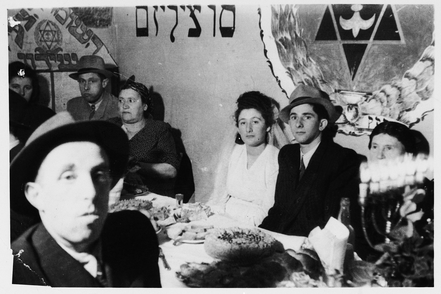 Wedding party of Yidl Weinstein and Gittl Zucker in the Windsheim displaced persons' camp.  A Hannuka menorah decorates the table.