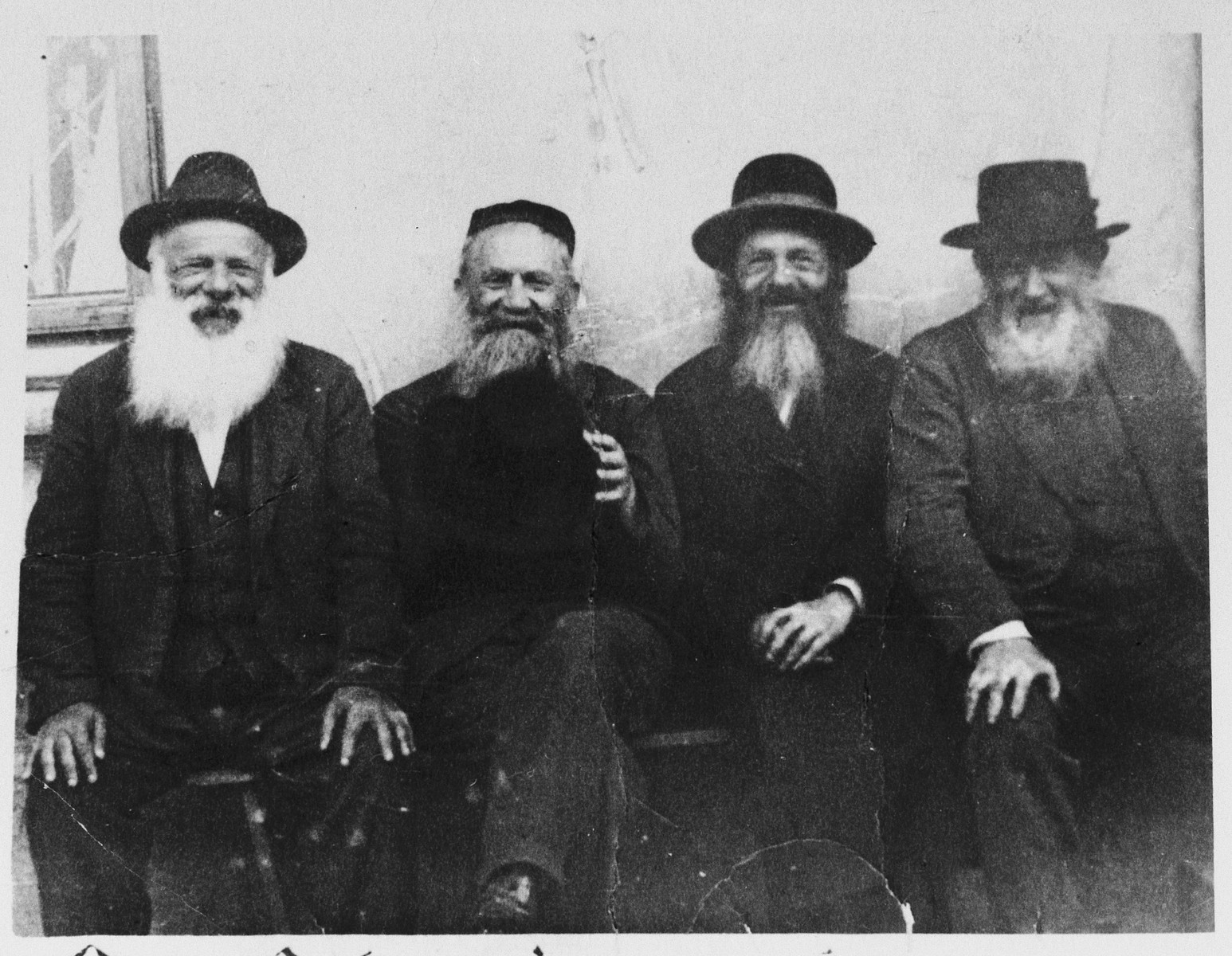Four elderly, religious Jewish men sit outside a building in Rudnik, Poland.  The father of Pinchos Wagner is second from the left.
