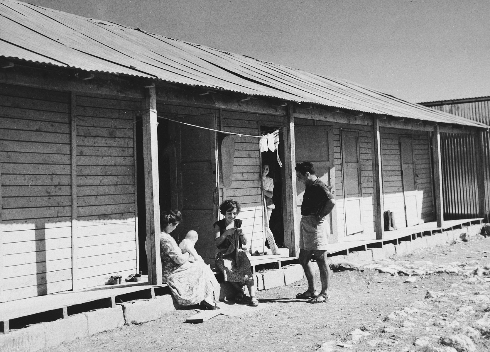 New immigrants sit on the stoop of their home in Tel Shachar while socializing with their neighbors.