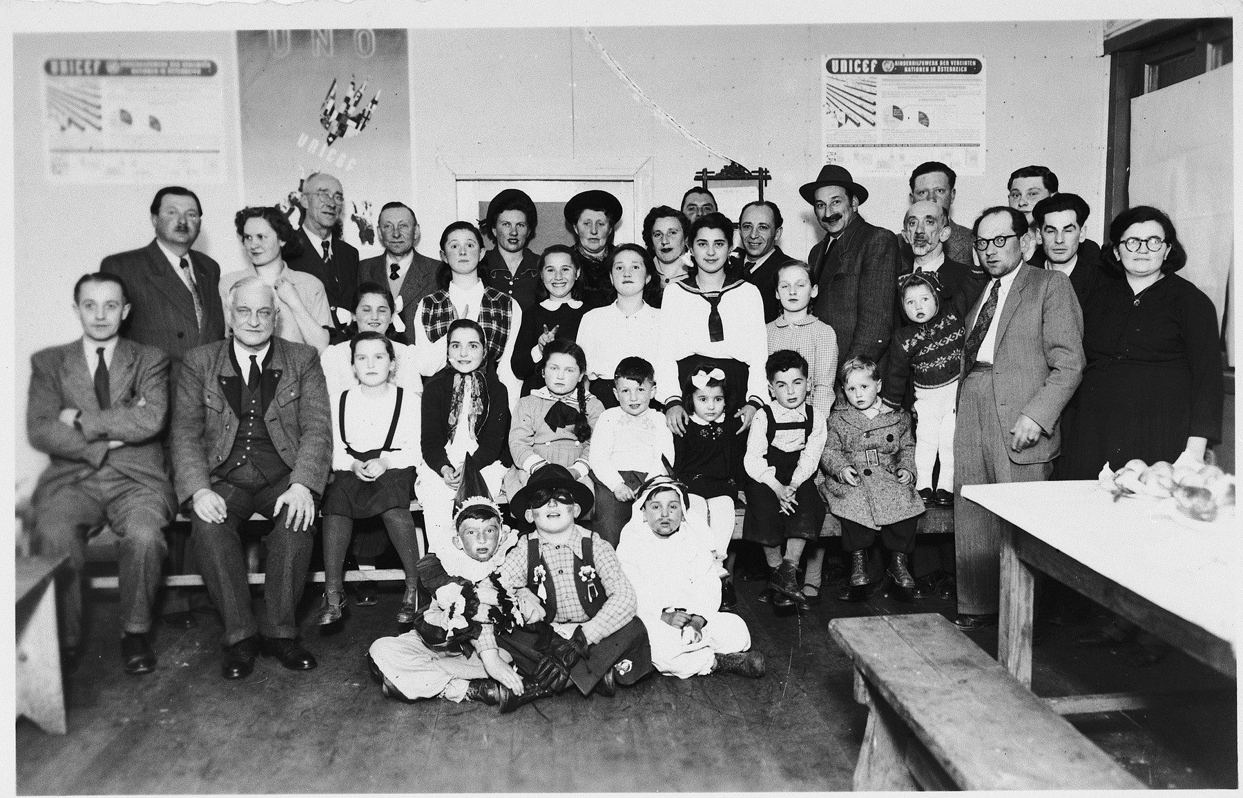 Children and adults in the Wels DP camp pose for a group portrait in their Purim costumes.