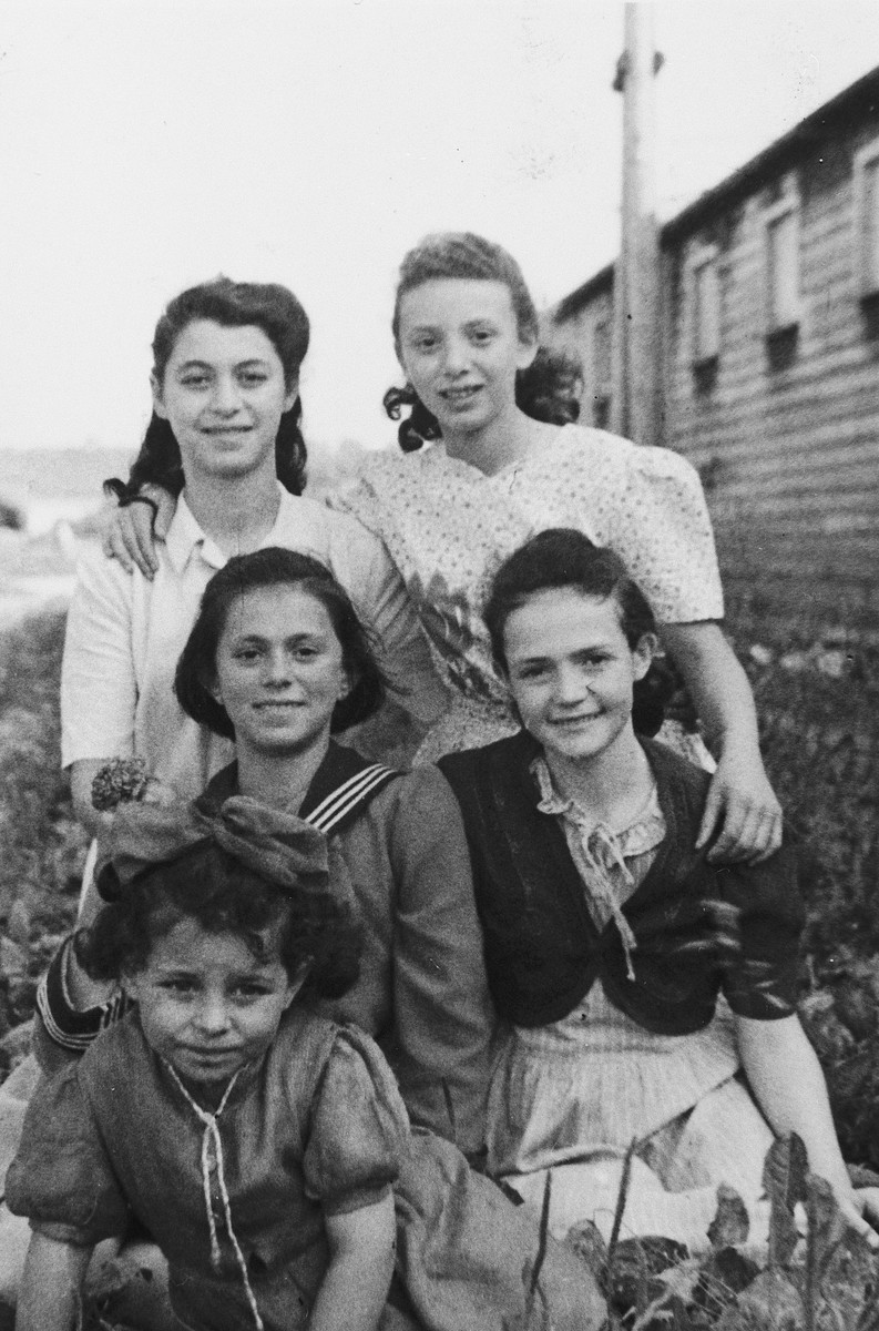 Five girls in the Wels displaced persons' camp pose in front of a barracks.  Pictured include Yehudit and Charlotta Wagner.