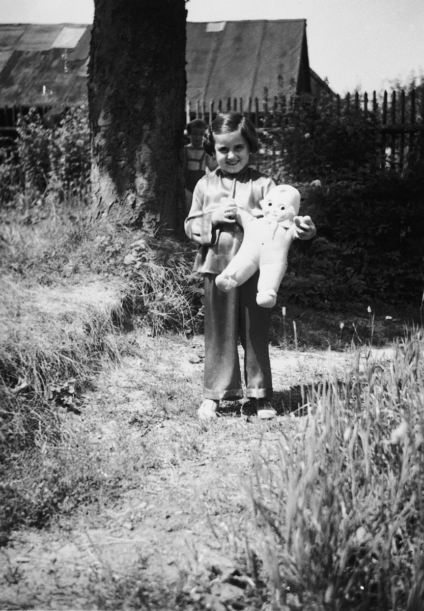 Portrait of Kitty Weichherz standing in a garden with her doll.  This photo was taken from the diary of Kitty's life written by her father, Bela Weichherz.