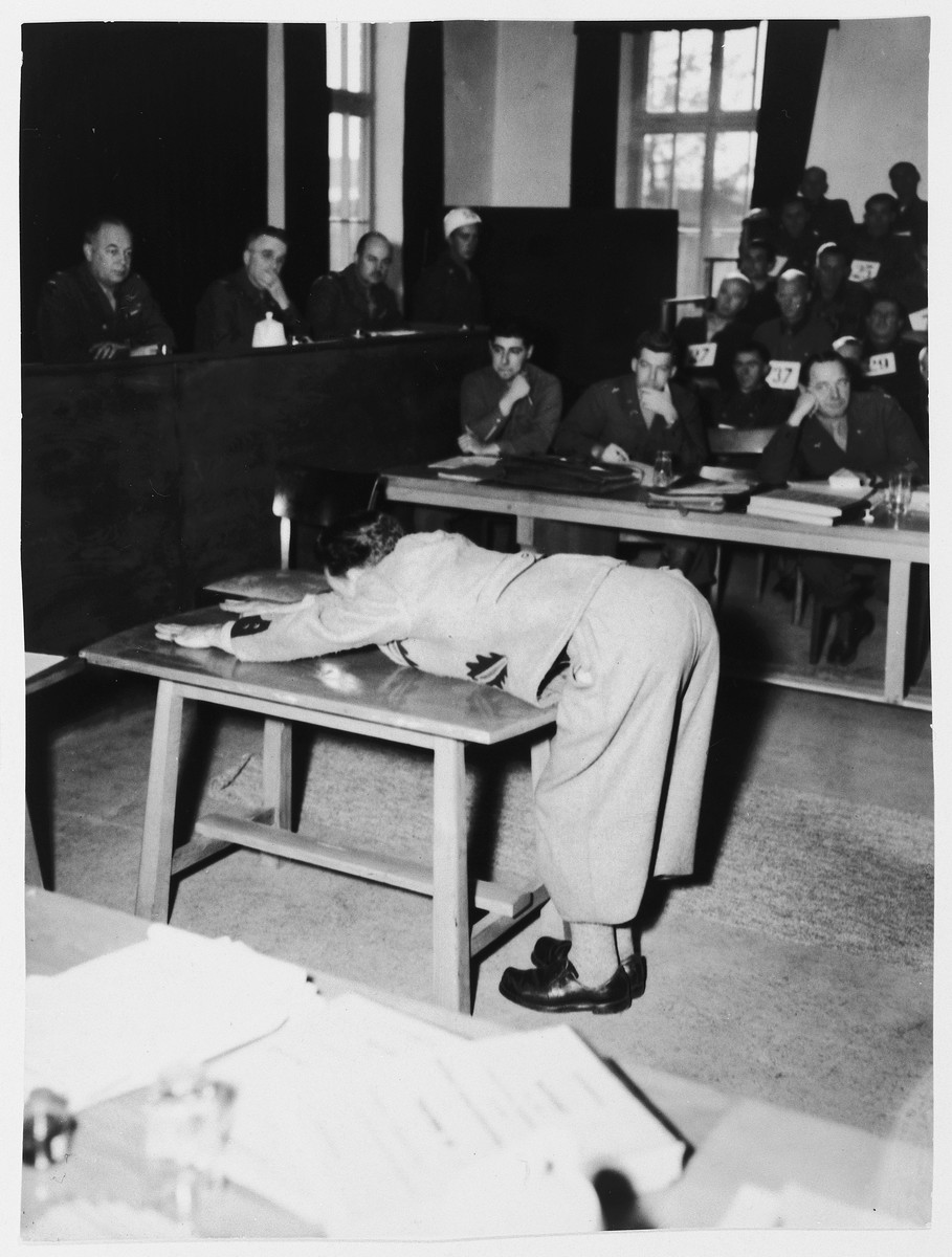 Prosecution witness Wolf demonstrates positions prisoners assumed for punishment on the whipping block in Dachau.