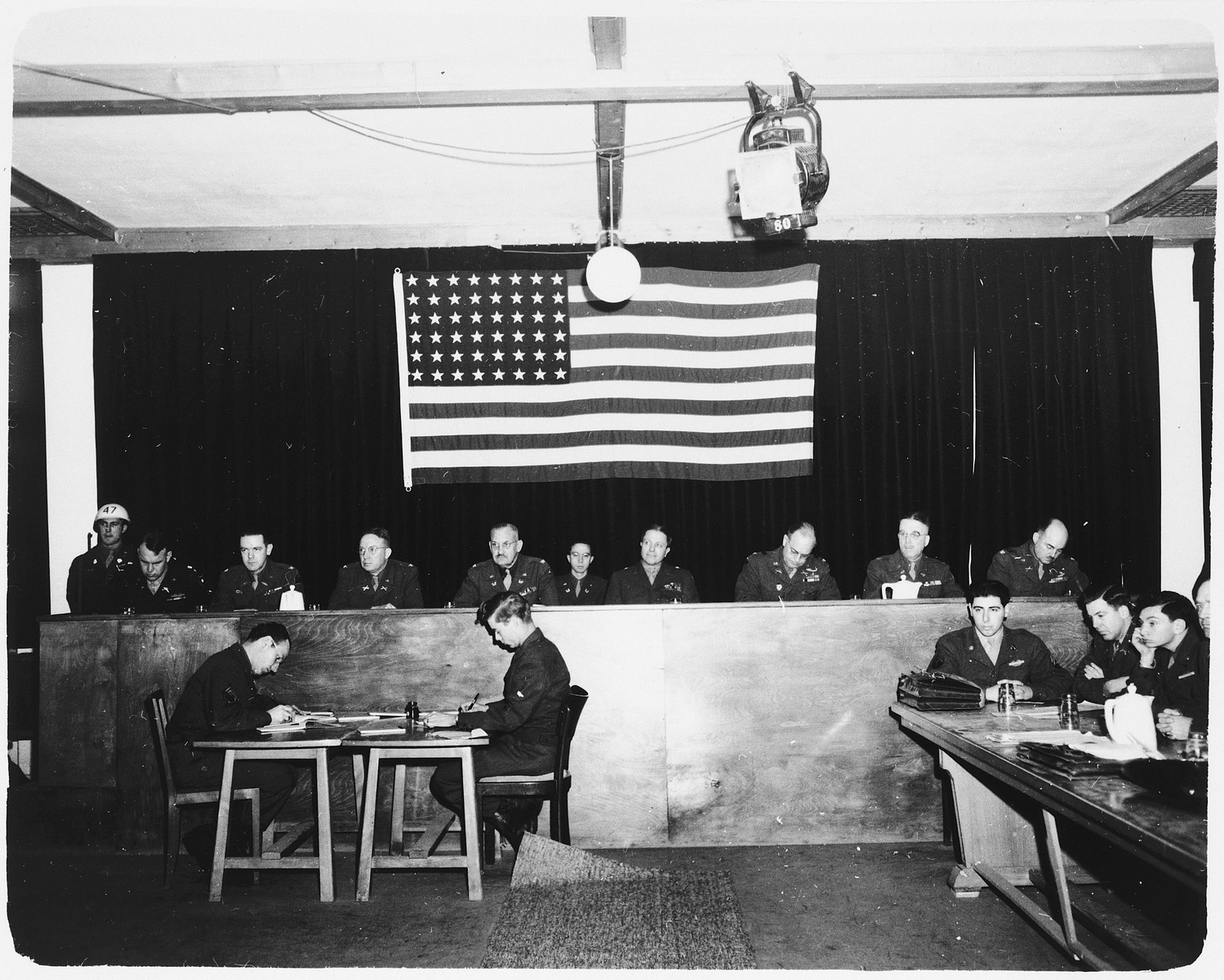 View of the judges bench of the Dachau trial.  A large American flag hangs behind them.  Interpreters for the defense sit at the table to the right of the judges. Among those pictured is Otto Ludwig Stein, third from the left, a 20 year old Sargeant in the US Army. Otto was a Jewish refugee that left Berlin in 1939 and immigrated to the United States. He joined the Army in 1944 and was given the choice of going to Europe or the Pacific, he chose Europe.