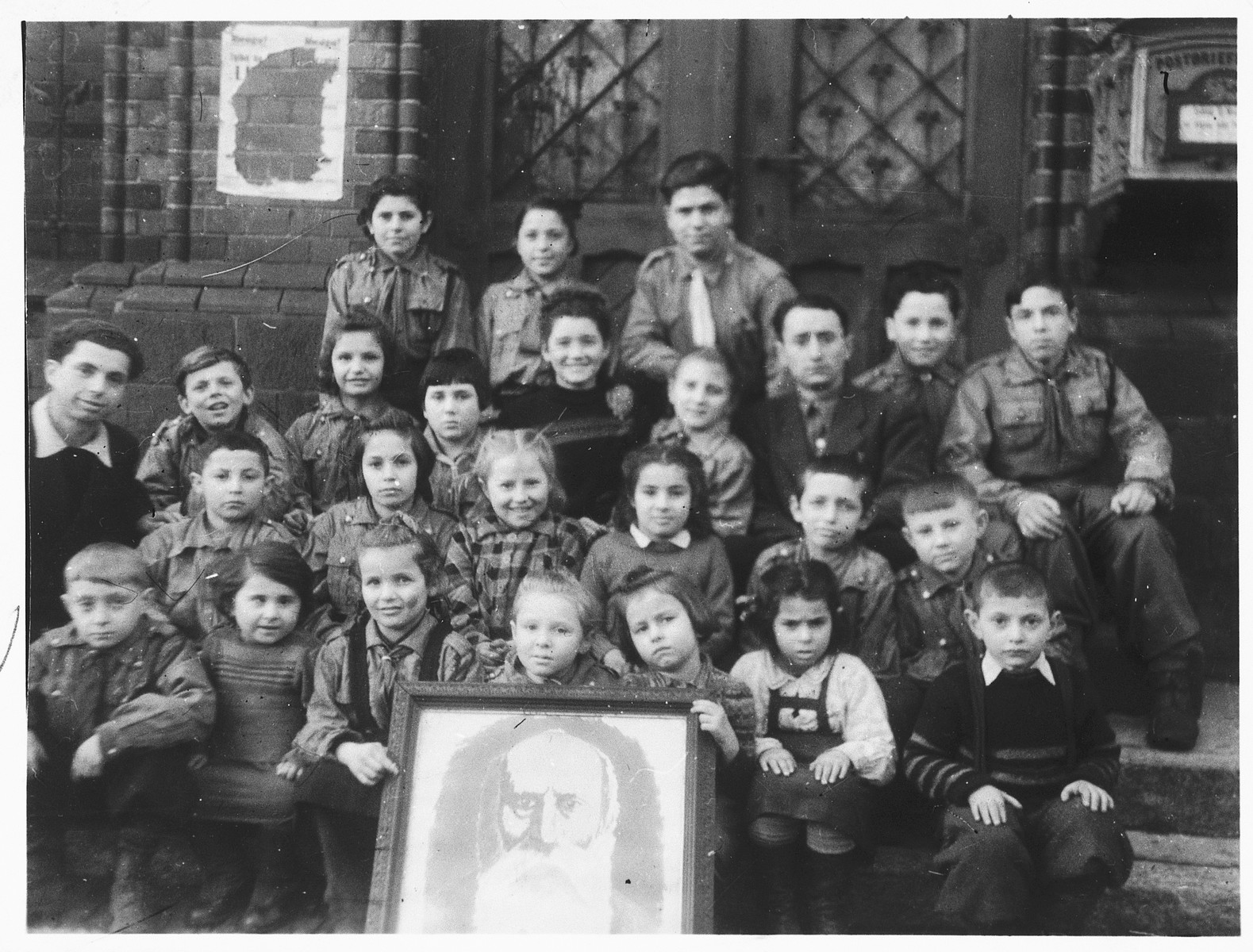 Children in a Gordonia Zionist youth group pose around a photograph of A.D. Gordon.  Charlotta Wagner is seated in the first row, third from the right.
