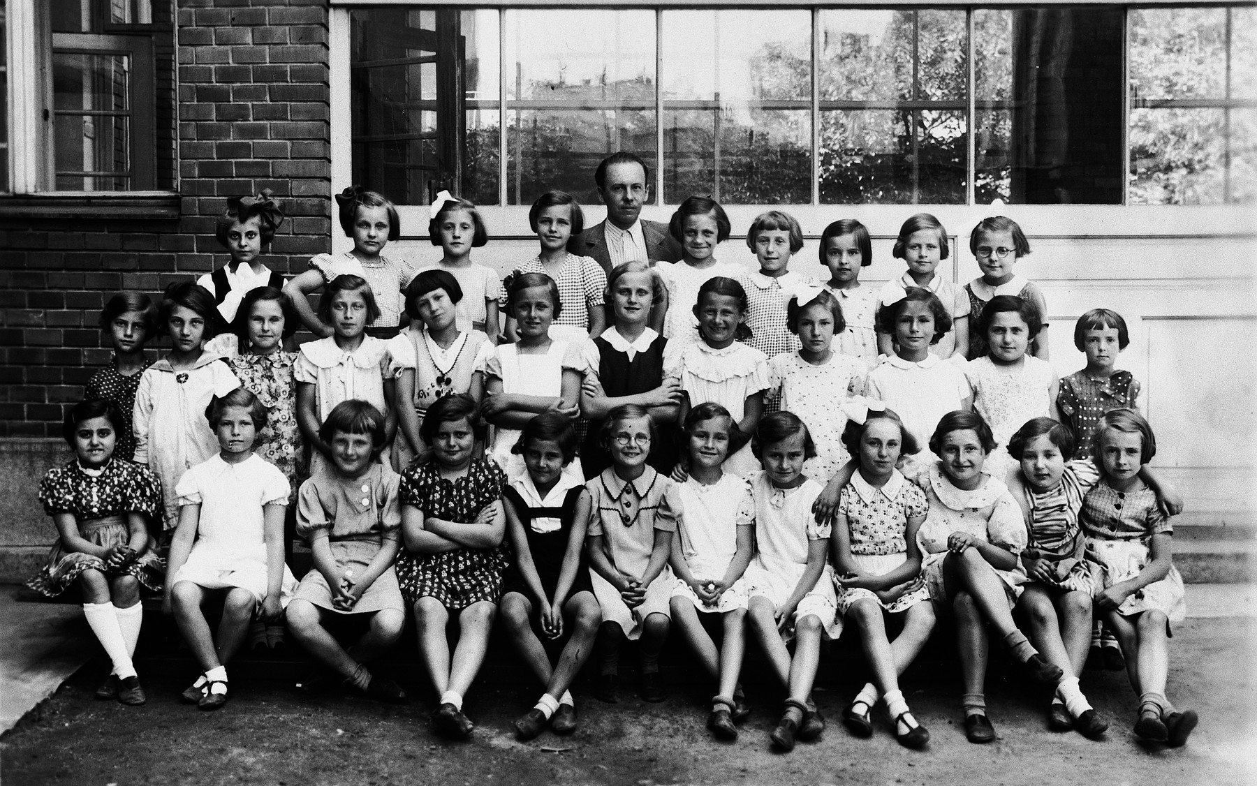 A group portrait of elementary school children in Bratislava.  Kitty Weichherz is sitting in the first row on the far left.  This photo was taken from the diary of Kitty's life written by her father, Bela Weichherz.