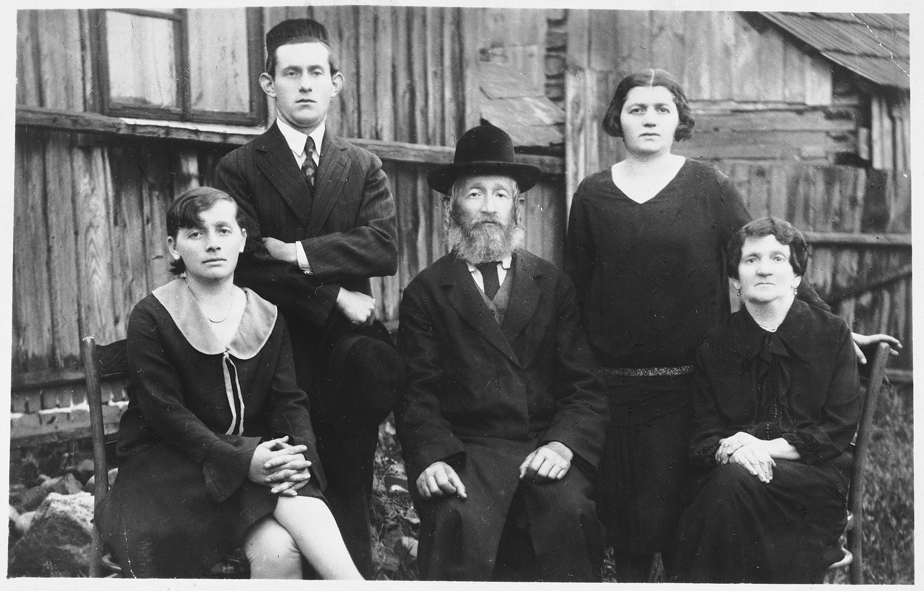 Members of a Jewish family pose outside in Kolbuszowa.  Pictured are Hersh (Sonel) Yaacov and Dobe (Mania) Kornbluth Silber (seated on the right) with their children, Rachel (seated front, left), Mosyc Aaron, and Bracha (standing in back).