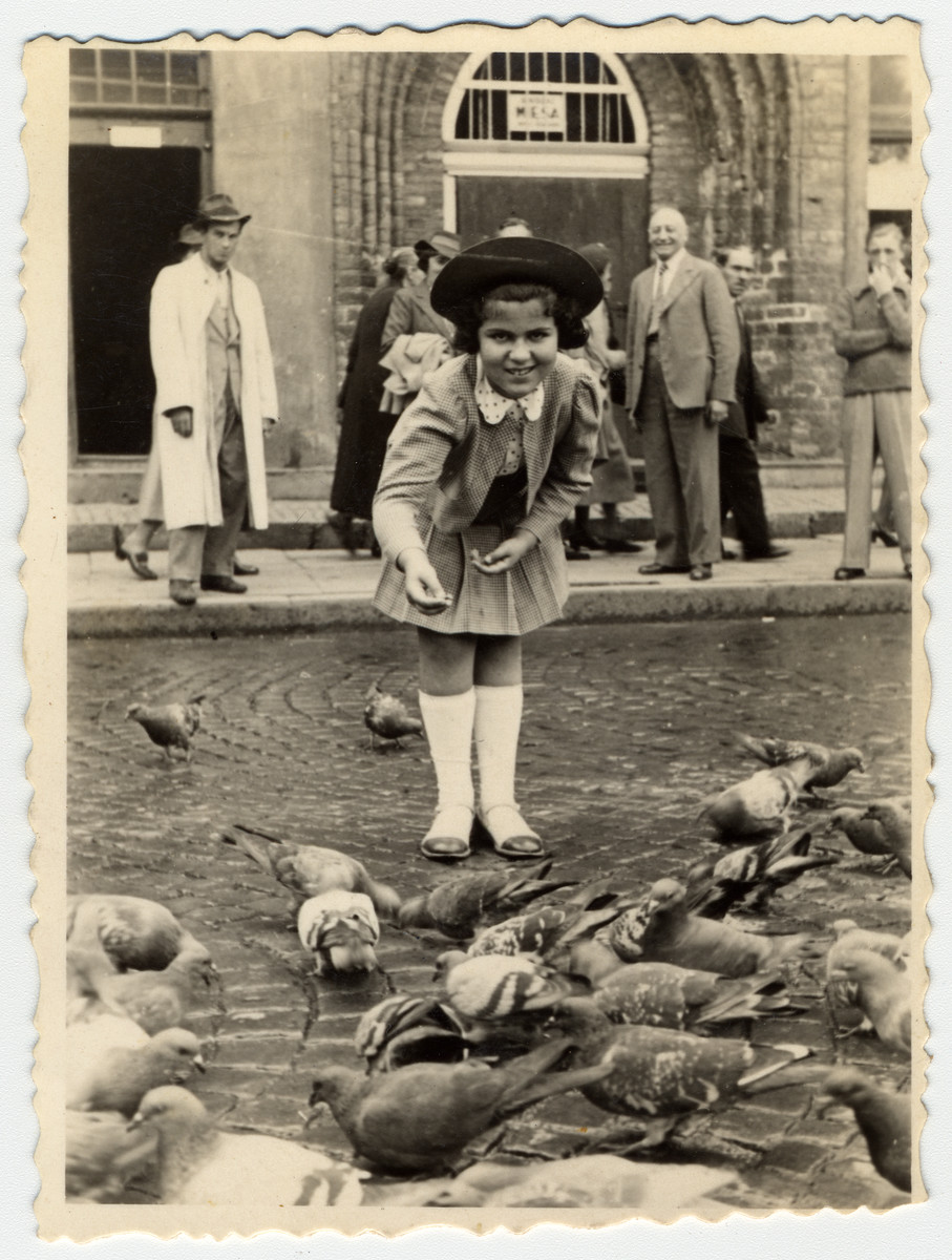 A young girl feeds pigeons in an public square in Warsaw.  Pictured is Inka Gerson.