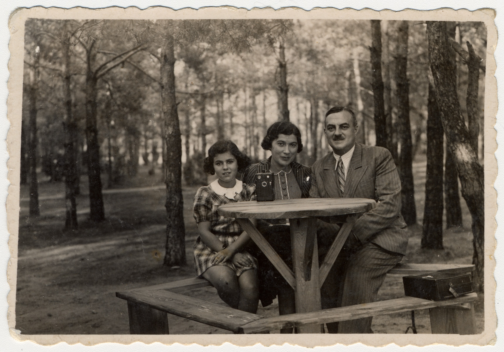 A Polish Jewish family sits around a picnic table in the woods near Lodz the summer before the start of World War II.  Pictured are Inka, Dora and Gustaw Gerson.