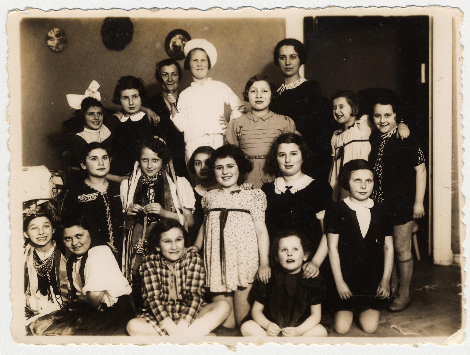 A group Polish Jewish girls, many of whom are wearing costumes, attend the 10th birthday party of Inka Gerson.  Among those pictured is Inka Gerson.  Her cousin, Janka Stillerman (later Yael Star) is wearing a cook's outfit.  The costumes with the ribbons and beads are a national Polish costume from the Krakow region.