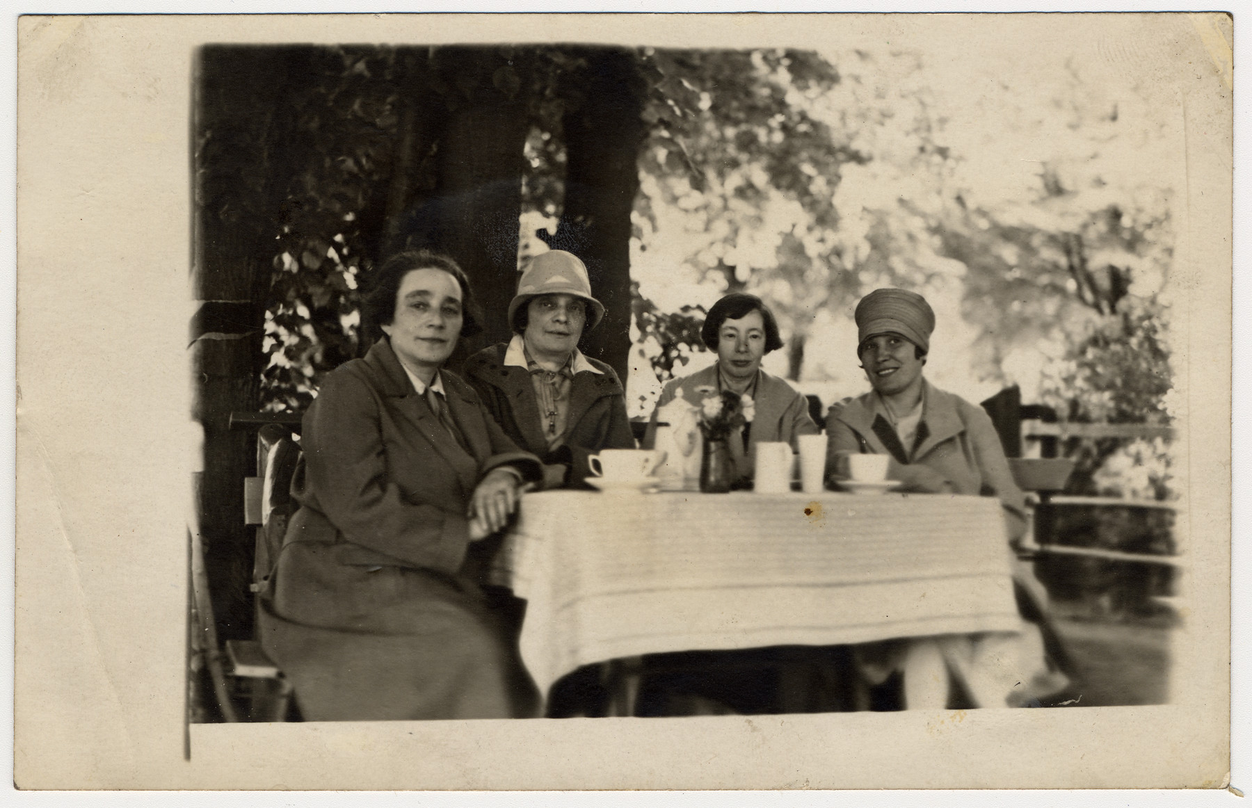 Four sisters enjoy a cup of coffee at an outdoor table.  From left to right are Anna, Martha, Clara and Beatrice Levy.  Anna died from natural causes in the mid 1930s. Her three sisters perished in the Holocaust in either the Mintz or Riga ghettos in 1941.