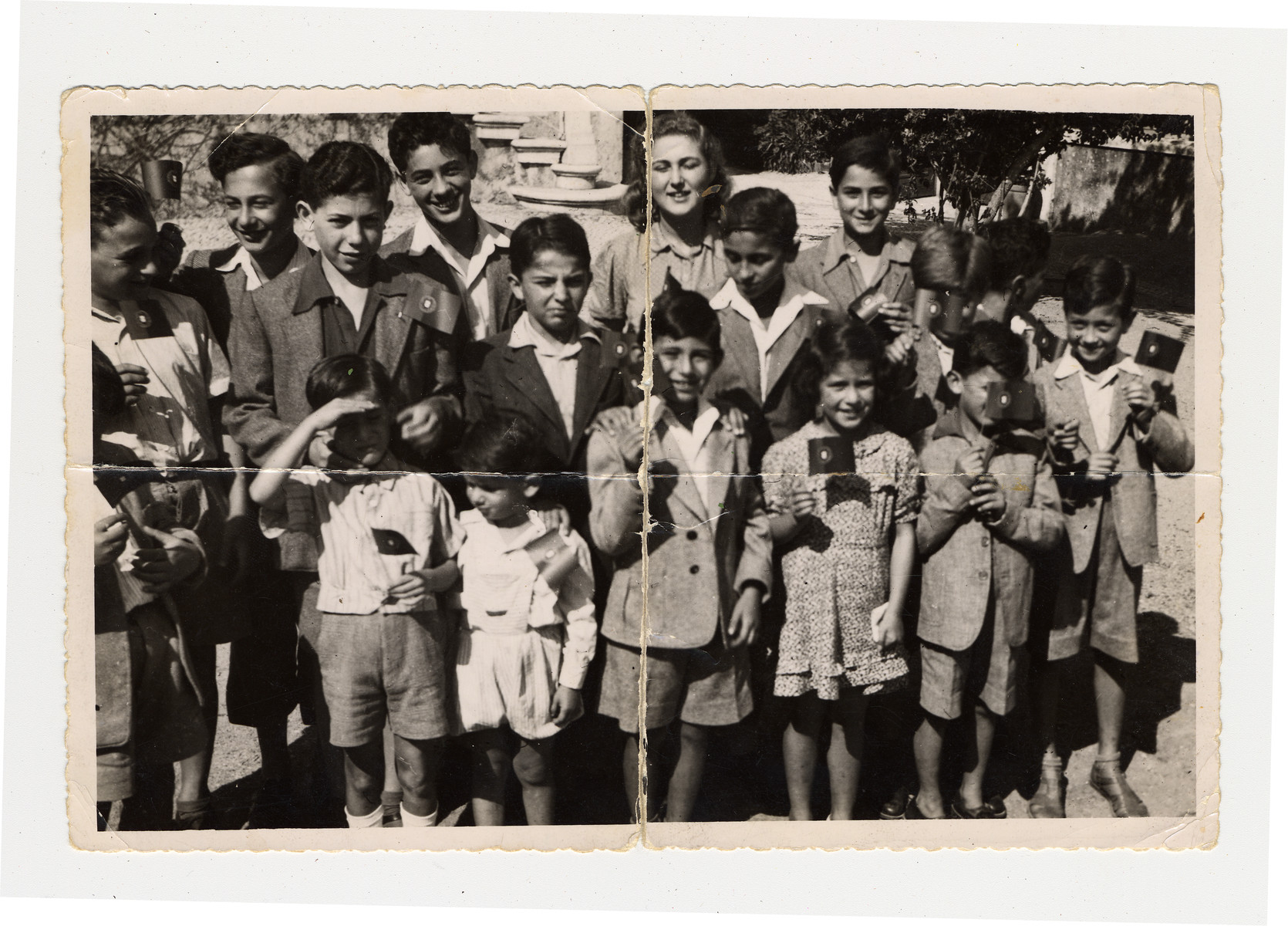 Group portrait of Jewish children in Lisbon where they are waiting to immigrate to the United States.  Manfred Manasse is pictured in the front row shading his eyes.  His brother Gustav is pictured on the far left.