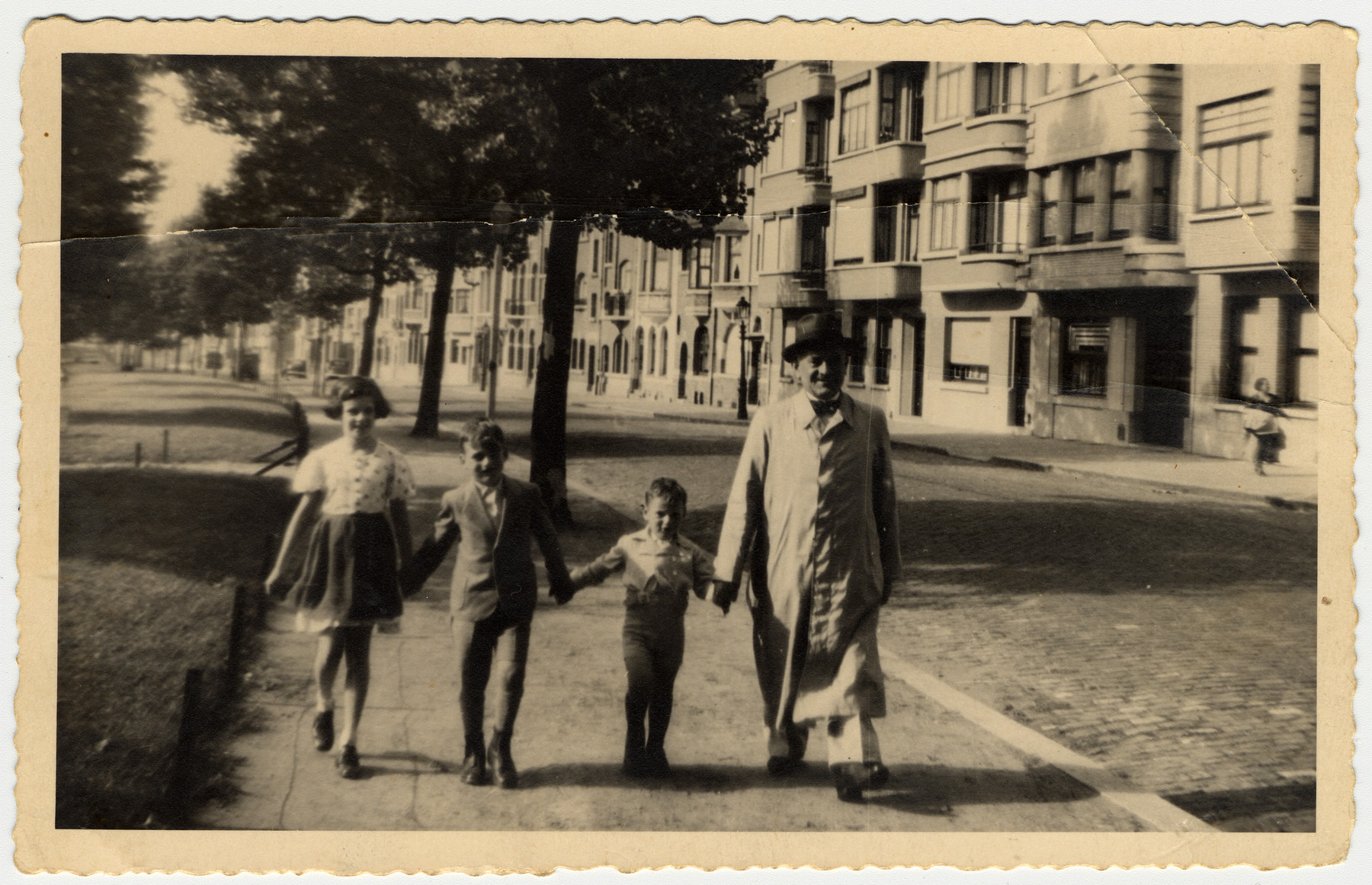 A father who had been a passenger on the St. Louis walks down a street in Brussels with his two sons and a friend.  Pictured from left to right are Marion Falik, Gustav Manasse, Manfred Manasse and Alfred Manasse.