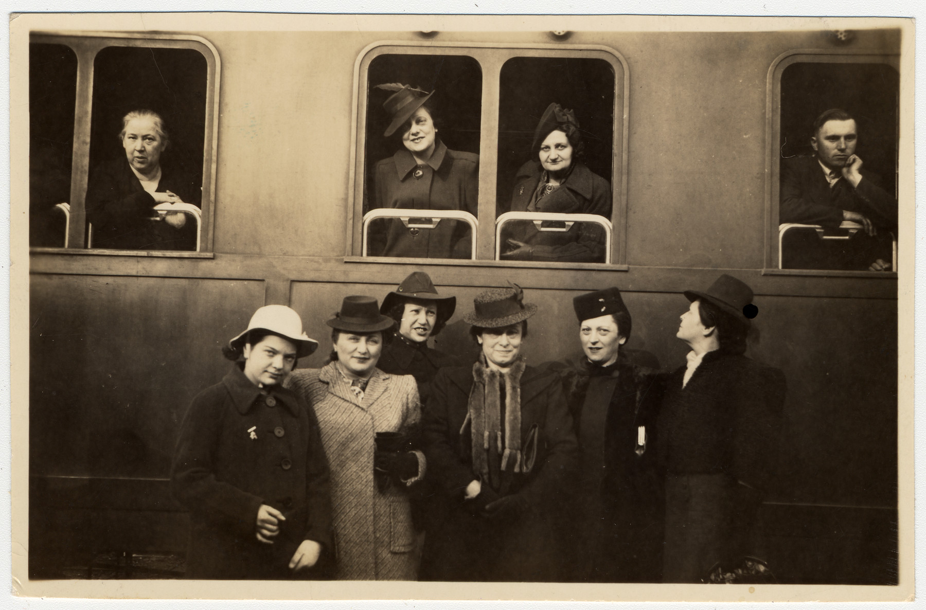 A group of women pose outside a train in the Budapest station.  Peering from the window is Lilly Brod who is about to depart for the United States.