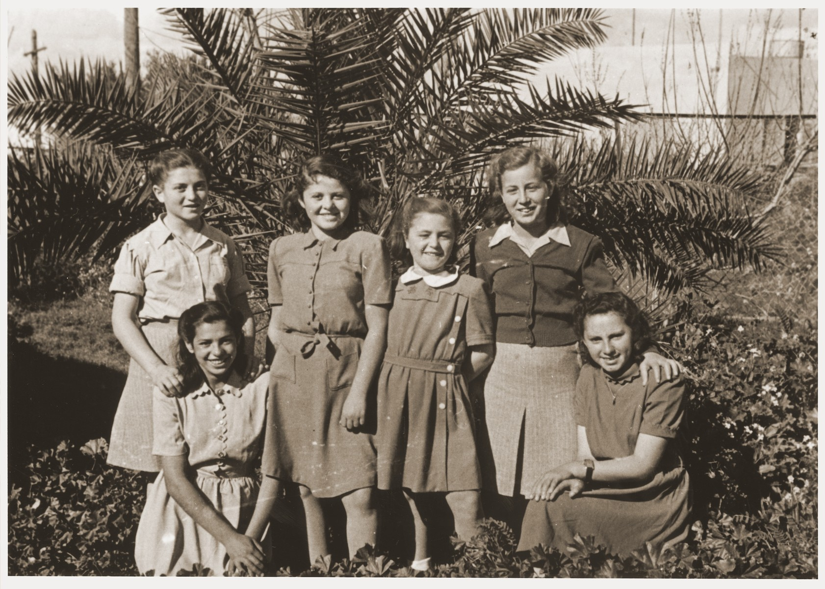 """Group portrait of former Transnistria orphans, now settled in Palestine due in part to the efforts of Anny Andermann.  The inscription on the back of the photo reads: """"A souvenir; the time passes quickly, the days follow each other, we write to you a souvenir because we don't know how long we will live, and as a sign of our love for you.  Anutza, Dora, Shana, Sarina, Gisella.  May God repay you, dear and good Mrs. Andermann."""""""