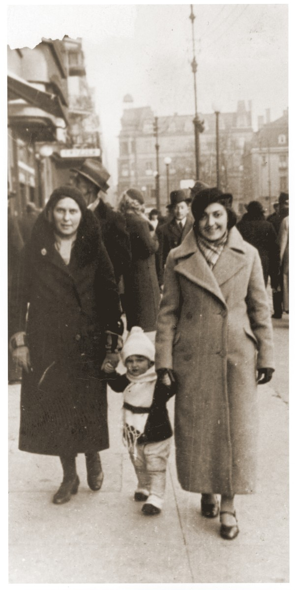 Salusia Goldblum walks between her mother Tola and aunt Nacha Broda on a street in Katowice.