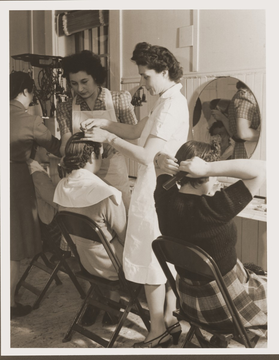 Mary Campo teaches a hairstyling class at the Fort Ontario refugee center.    45 refugees registered for the 240 hour course, in which the students learned to wash and set hair, give permanents, and do manicures and facials.