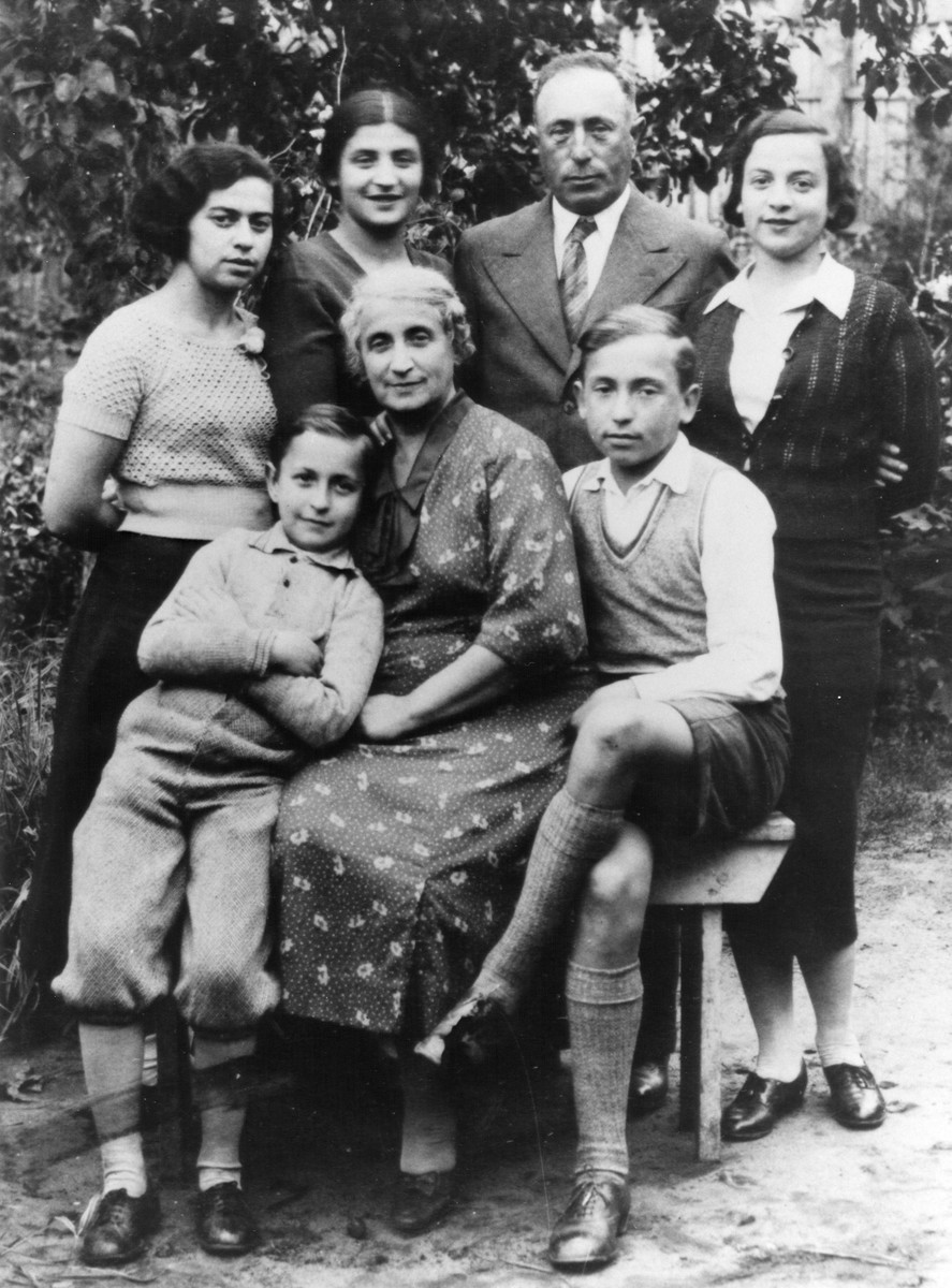The Birger family poses in a garden in Kaunas.   Zev is standing in knickers beside his mother Zipporah (Feiga).  His brother Mordecai (b. 1923) is to her right.  Standing from left to right is Bella Chait, Bella Hamburg Adler,Zev's father Pinchas and Rivka Hamburg.  Of those pictured only Zev Birger and Bella Adler survived.