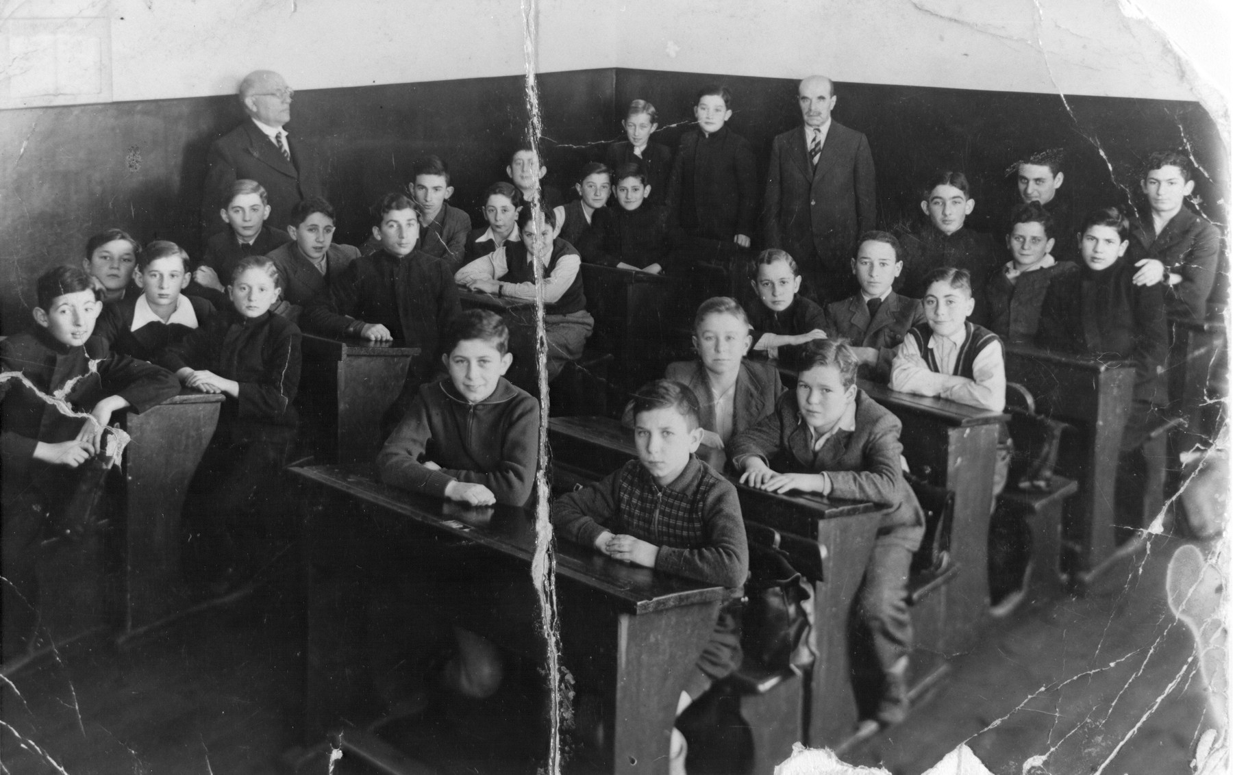 Class of the Real Hebrew Gymnasium, the first Hebrew high school in Kaunas.    Mr. Dumblansky, the Hebrew teacher, stands in the back of the room.  Those seated include Zev Birger, Fima Strom, Micklishansky, Memko Rubin, and Motke Fischer.