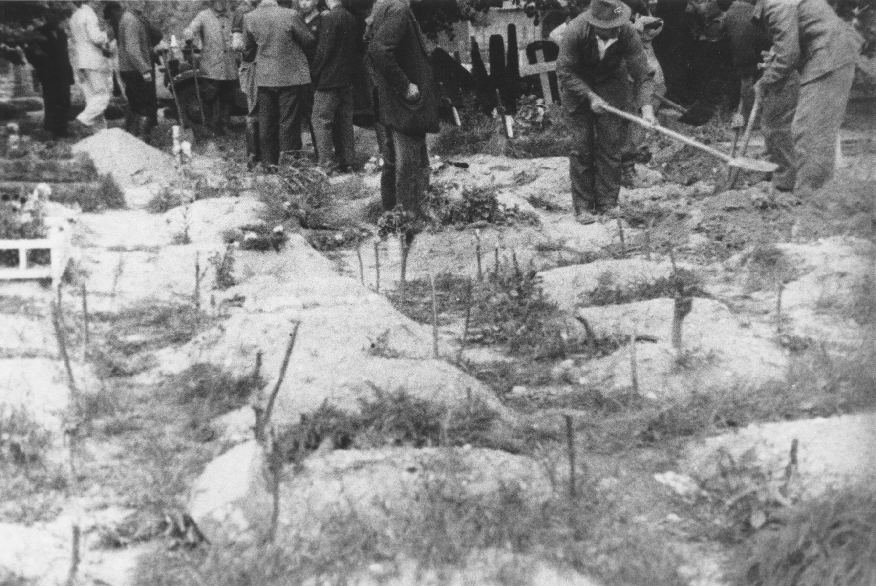 German civilians rebury the exhumed remains of the Polish and Soviet infants who died in the nursery in Ruehen.