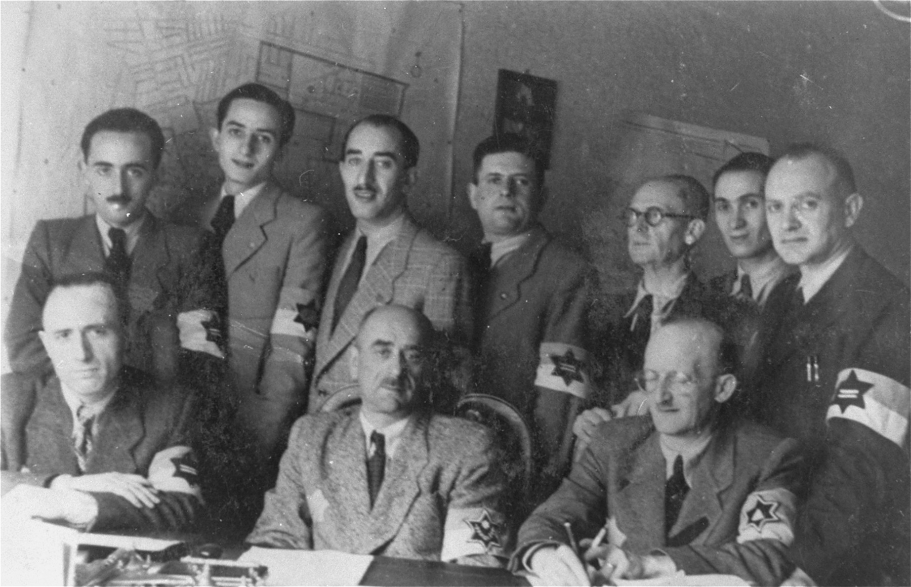 Group portrait of members of the Lodz ghetto police.     Among those pictured is Leon Rozenblat, chief of the police (seated in the middle), Dr. Piotrkowski (seated on the left) and Julek Grosbart (seated on the right).  Hermann Chimowicz is in the middle of the second row.