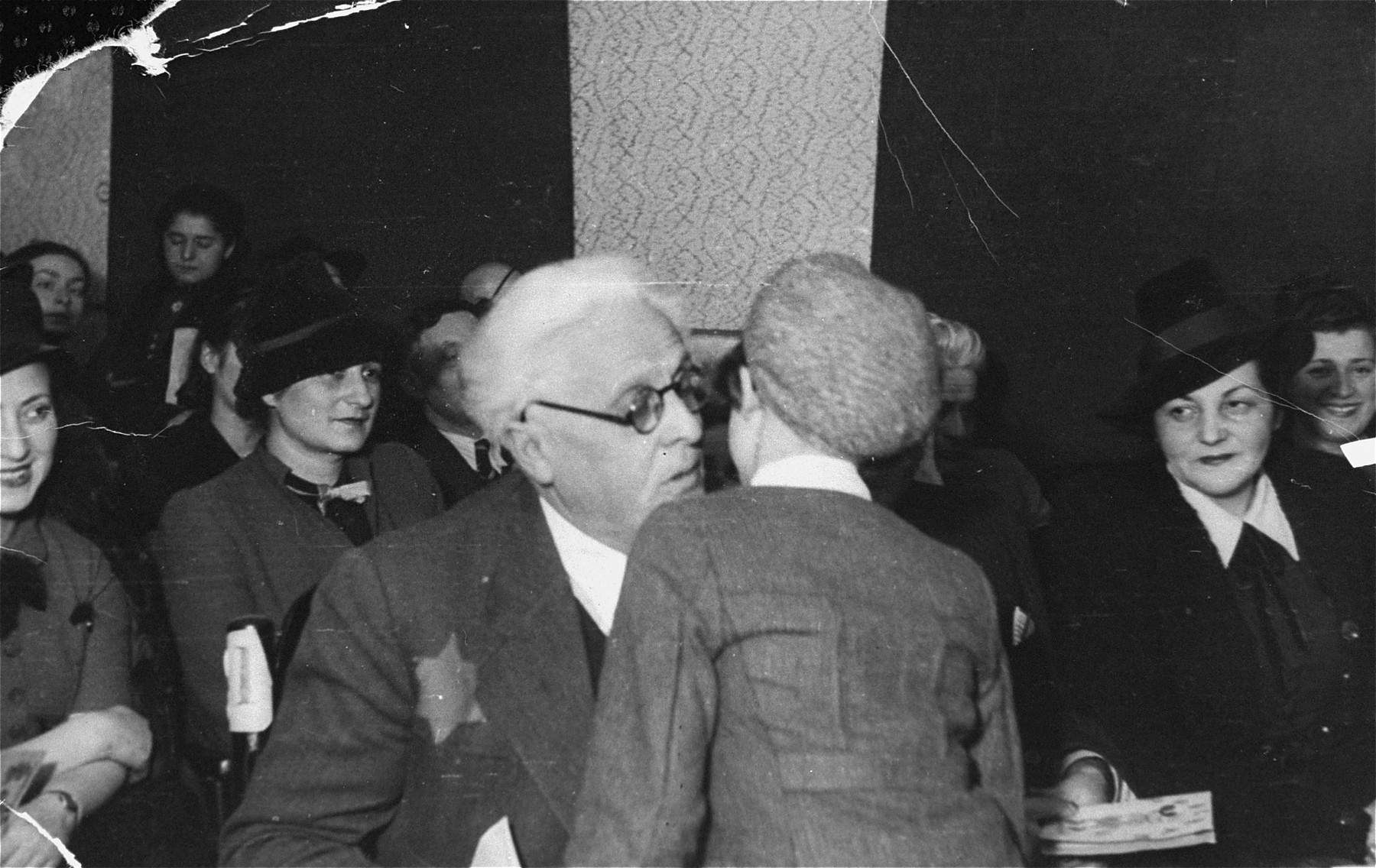 Jewish council chairman Mordechai Chaim Rumkowski, greets a child at a school ceremony in the Lodz ghetto.    Also pictured is Helena Rumkowska (at the left).