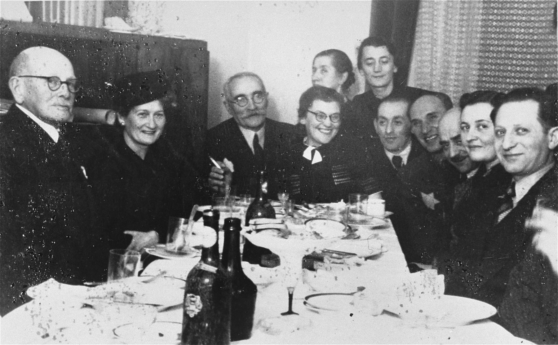 Wedding celebration of Manya Milderman Praszker and Baruch Praszker in the Lodz ghetto.  The bride and groom are seated at the head of the table.  Baruch's mother, Chaia Esther Praszker is behind Mania and next to her is Mania's sister, Ruth Milderman Praszker.  Baruch Praszker was a leader of the religious Zionists and head of the cemetery department in the ghetto.
