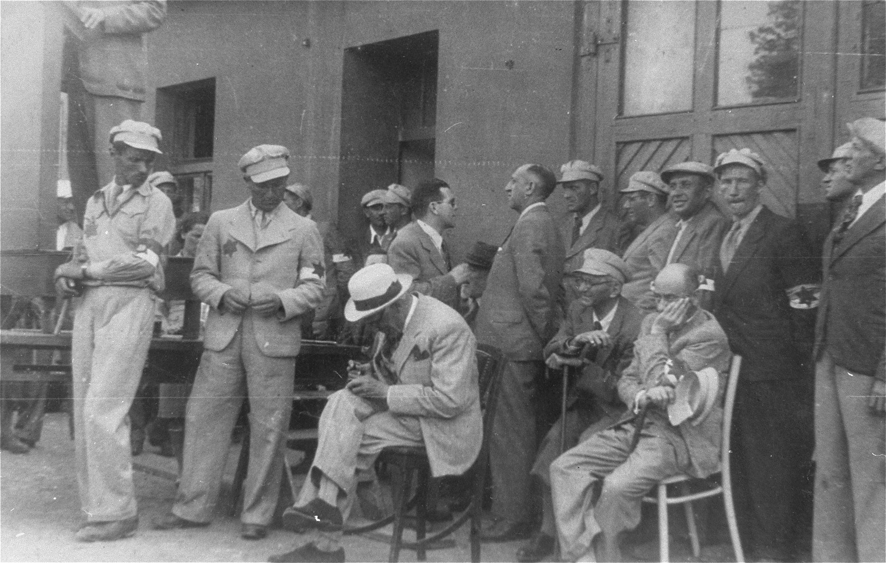 Mordechai Chaim Rumkowski (seated in the center), attends an event with members of the Jewish police and Sonderkommando.  Also pictured is Leon Rozenblat (seated at the right, holding his cap).  The man behind Rumkowski may be Stanislaw Jakobson.