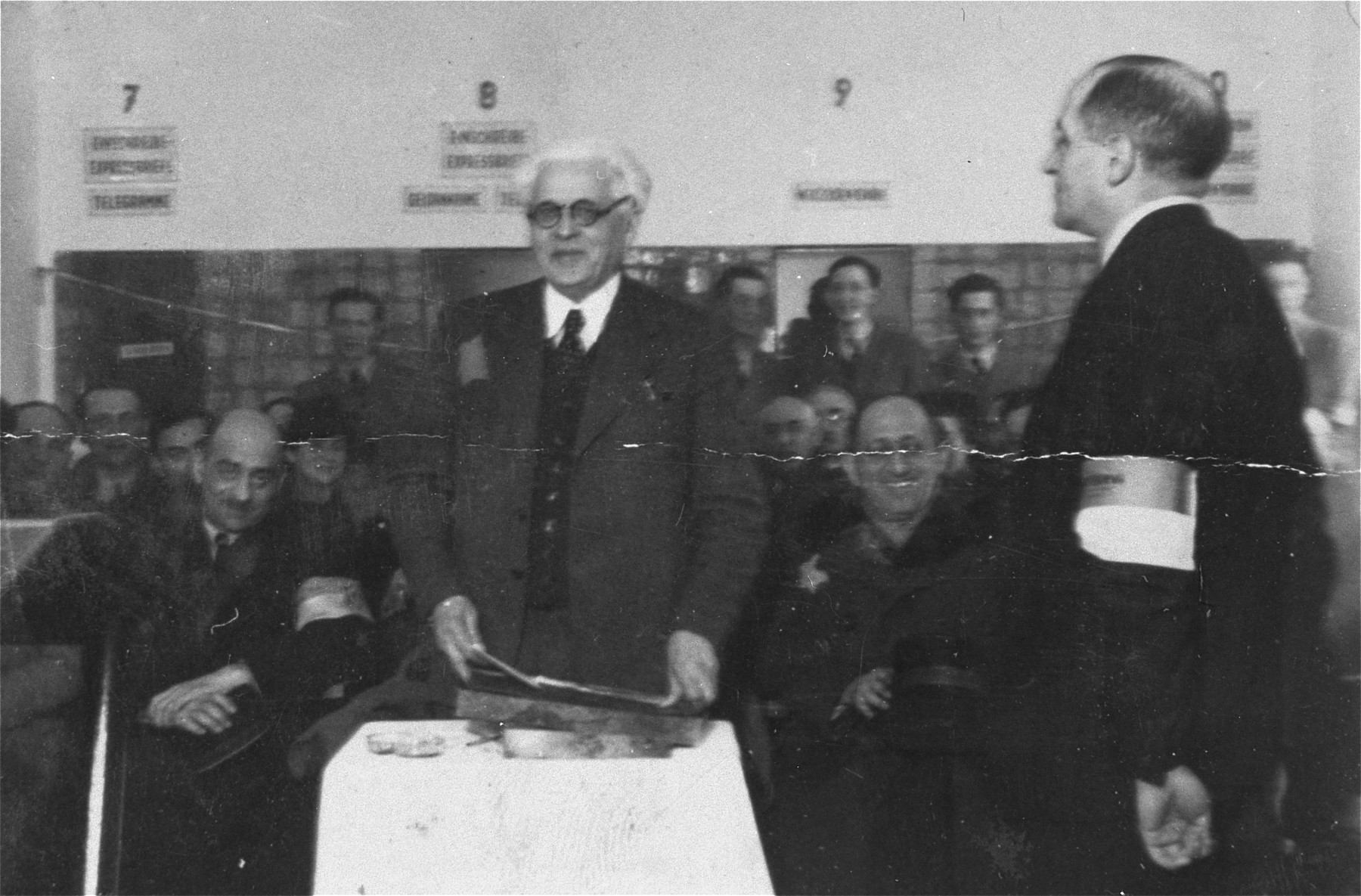 Jewish council chairman Mordechai Chaim Rumkowski, delivers a speech after receiving a presentation album at a ceremony in the Lodz ghetto.    Among those pictured are Leon Rozenblat (seated on the left) and Dr. Leon Szykier (stands on the right).