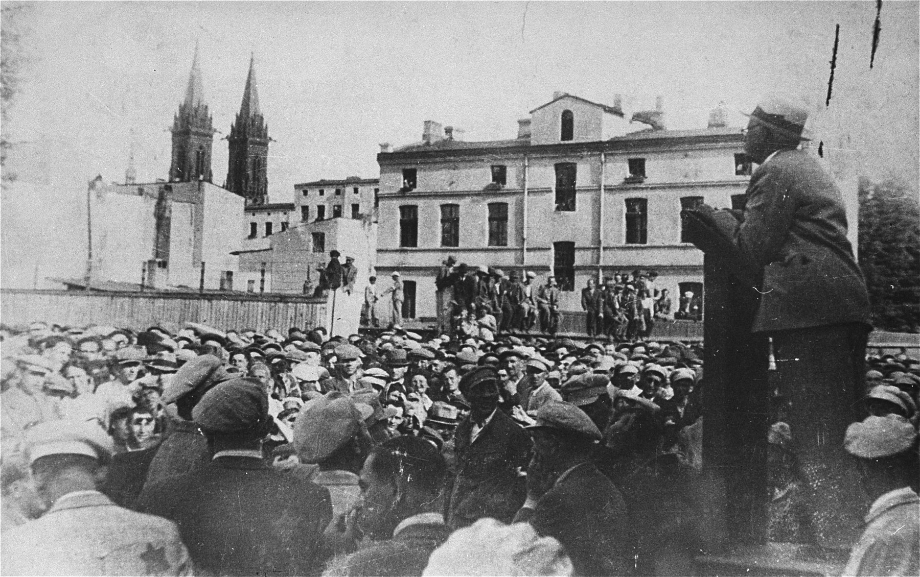 Mordechai Chaim Rumkowski, chairman of the Lodz ghetto Jewish Council, delivers a speech to a crowd of Jews gathered in a public square on Lutomierska Street in the Lodz ghetto.