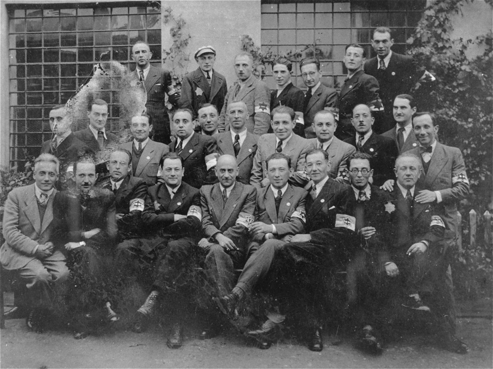 Group portrait of members of the Lodz ghetto police.   Among those pictured is Leon Rozenblat, chief of the Lodz ghetto police (front row, center).  Abram Josef (Alfred) Chimowicz is sitting immediately left of Leon Rozenblat.