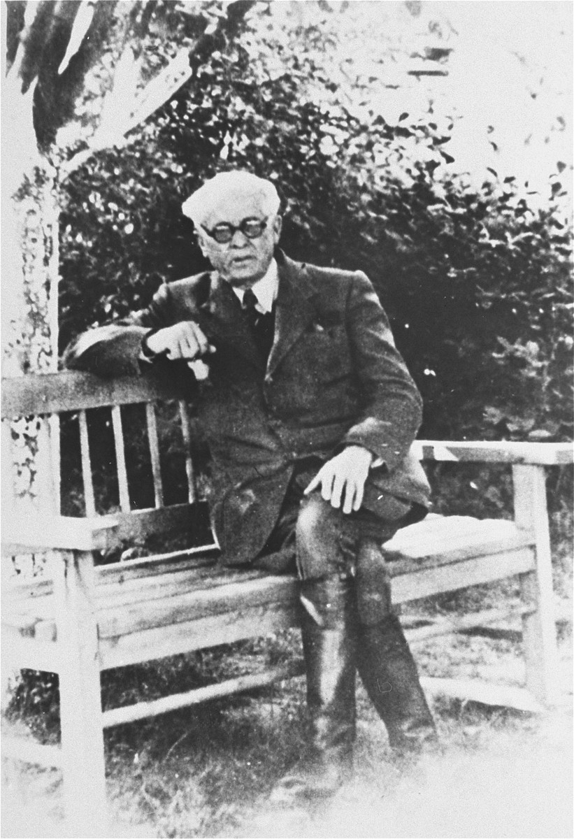 Portrait of Mordechai Chaim Rumkowski, chairman of the Lodz ghetto Jewish Council, seated on a bench.