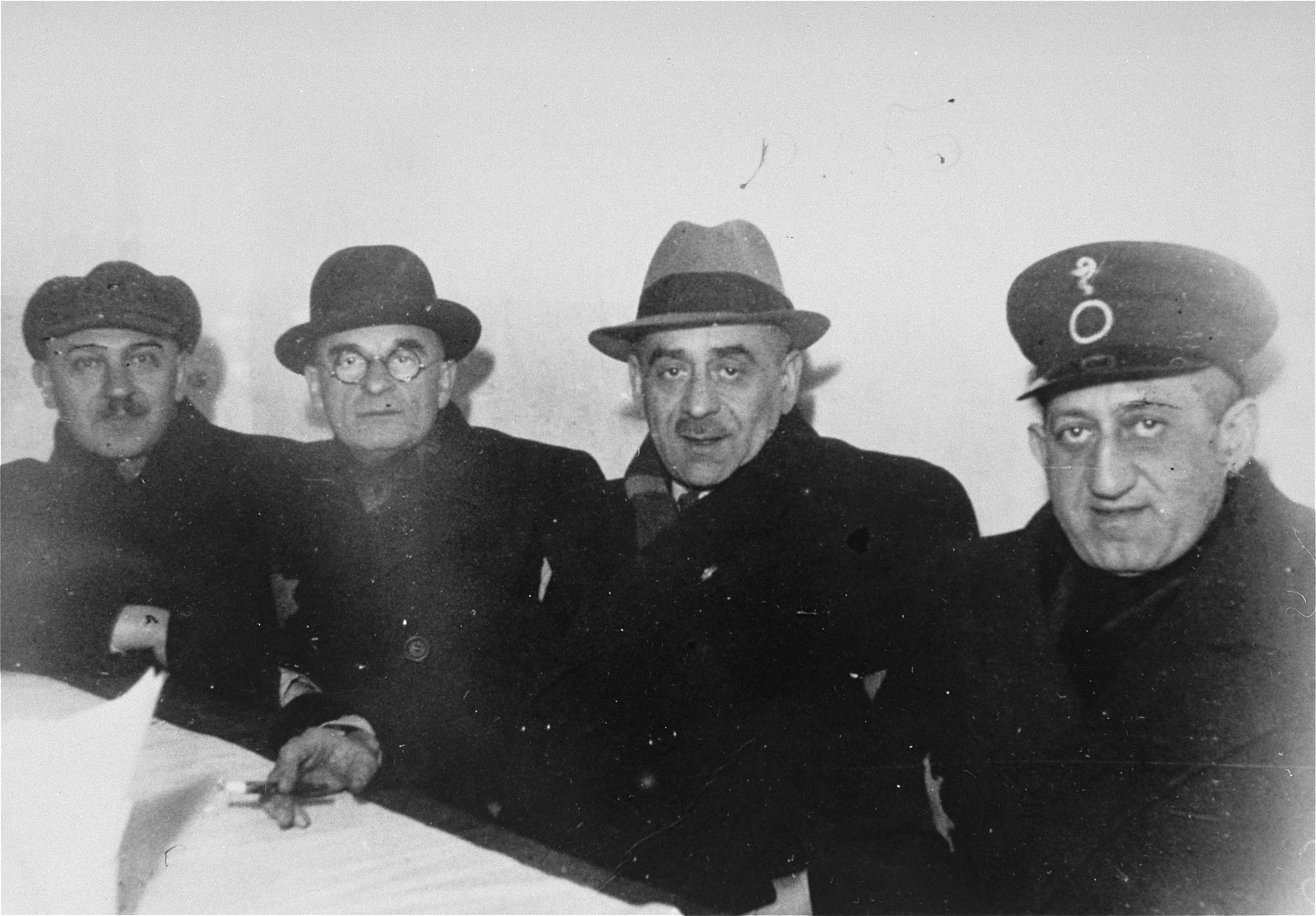 Four members of the Lodz ghetto administration seated at a table.  Pictured from left to right are: Mordechai Lajzerowicz, head of the ghetto bakeries; Max Szczesliwy, head of food supply; Leon Rozenblat, chief of police; and Dr. Leon Szykier, head of the health department.