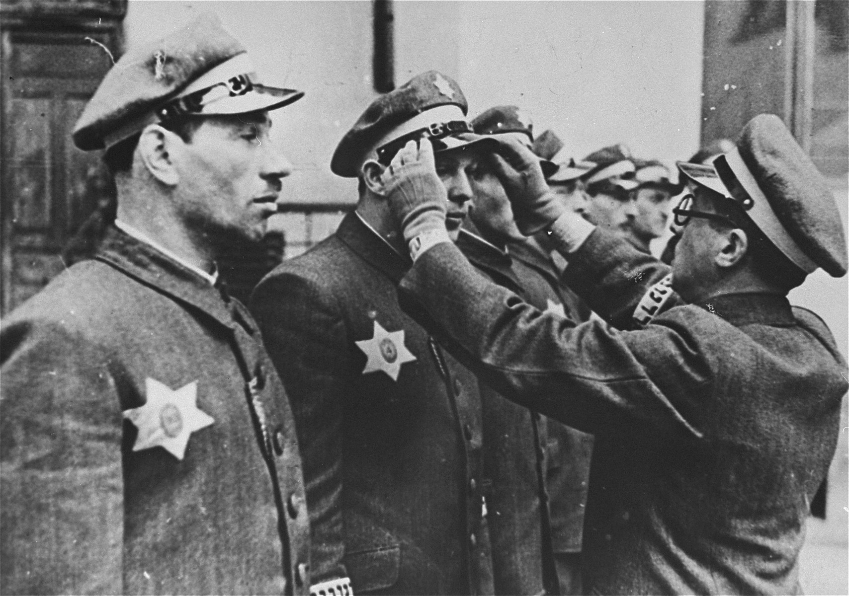 "Symche Spira, the senior officer of the Krakow ghetto police (Ordnungsdienst) straightens the cap of one of his men during roll call.    Members of the Ordnungsdienst in Krakow wore unique identifying marks as part of their uniform.  These included armbands on which ""Ordnungsdienst"" was written in Hebrew and badges in the shape of the Star of David surrounding an oval that gave the officer's number.  OD officers assisted in the deportation of Jews from the Krakow ghetto, among other tasks, and the last of its members were themselves deported to the Plaszow labor camp when the ghetto was finally liquidated in March 1943.  Spira who was later replaced by Wilek Chilowicz ."