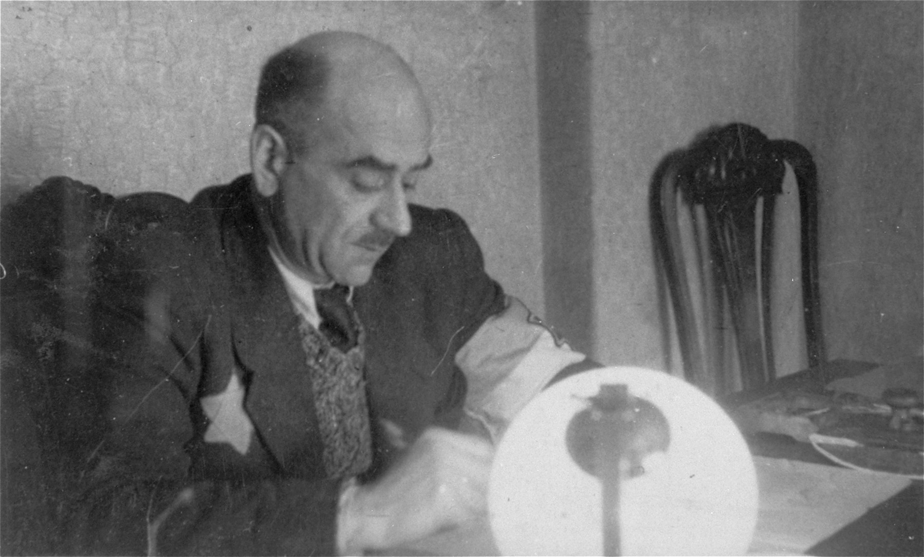 Leon Rozenblat, chief of the ghetto police, is seated in his office in the Lodz ghetto.