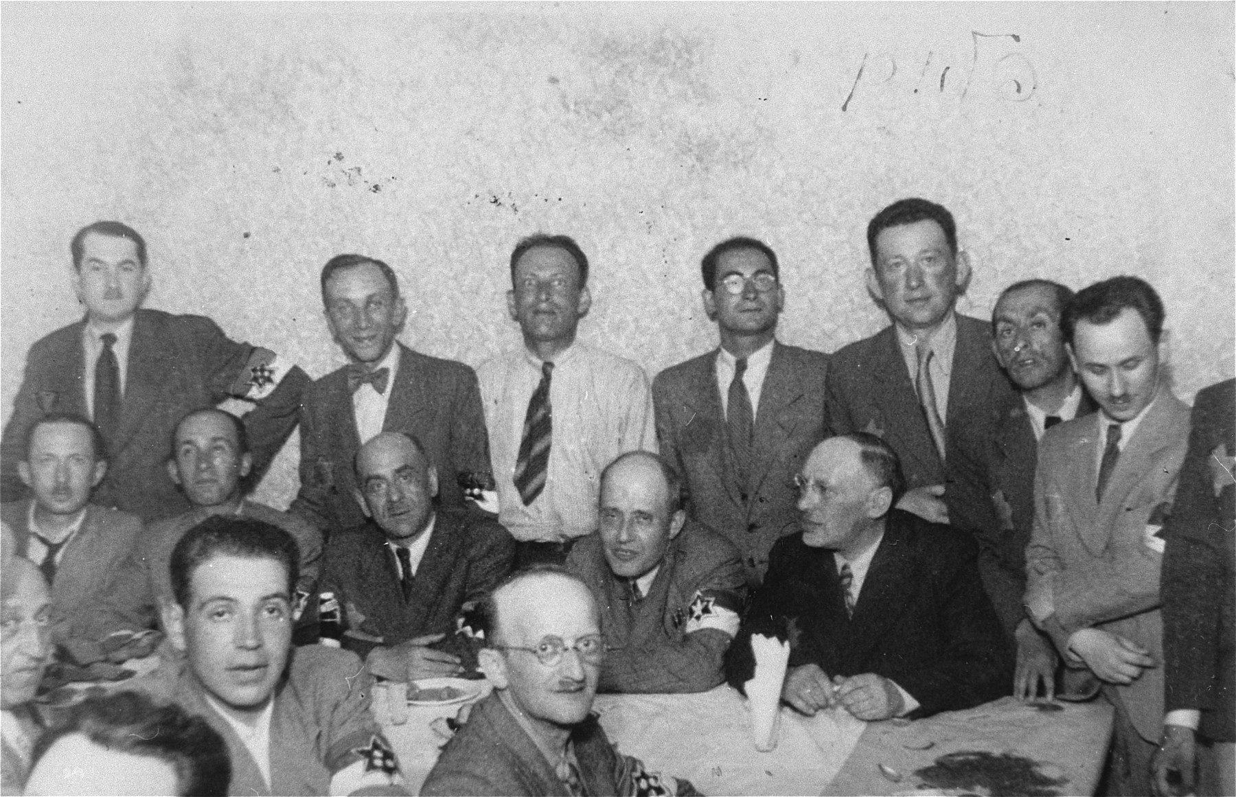 Members of the Lodz ghetto administration, including heads of workshops, police and members of the Sonderkommando, at a social gathering.  Among those pictured are: Leon Fajtlowicz, in charge of the leather workshops (standing fourth from the left), Zygmunt Reingold, director of food supply (standing fifth from the left), Baruch Praszker, chief of special assignments (standing second from the right),  Leon Rozenblatt, chief of the ghettto police (seated on the far side of the table, third from left) and David Warszawski, director of the tailoring workshops (seated on the far side of the table, first from right).