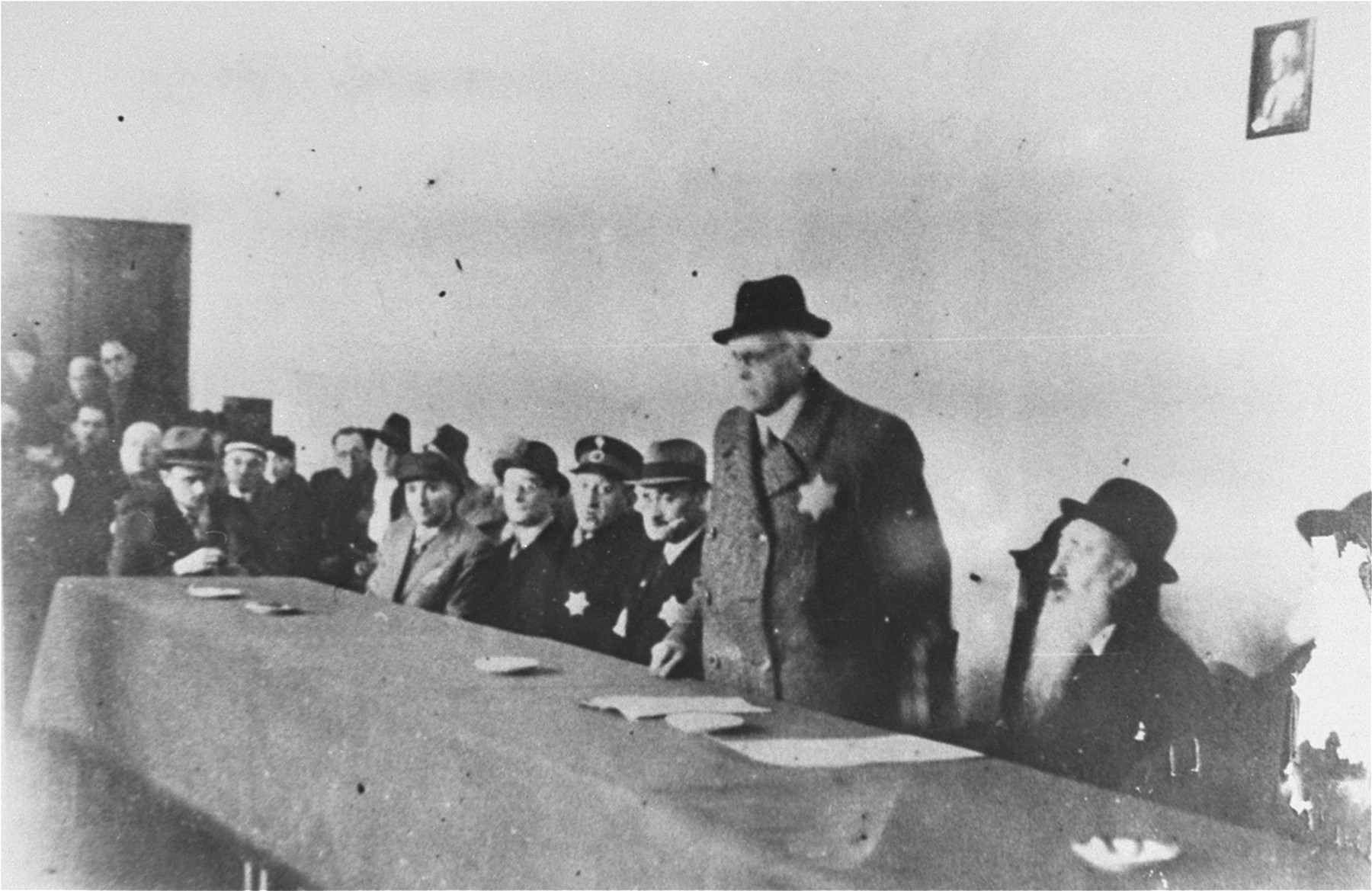 Mordechai Chaim Rumkowski delivers a speech at a meeting of Lodz ghetto officials.    Among those pictured are: Rabbi Josif Fajner (second from the right), Dr. Leon Szykier (fifth from the right, wearing a uniform cap).