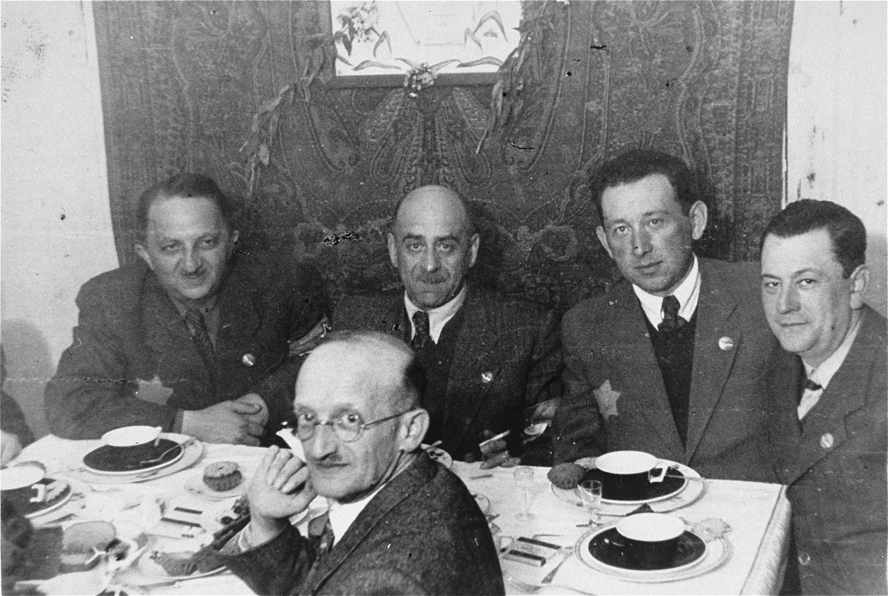 Members of the Lodz ghetto administration are gathered around a table.  Seated on the far side of the table are: Leon Rozenblat, chief of the ghetto police (third from the right), Zygmunt Reingold, head of food supply (second from the right), Jozef Chimowicz, head of the metal workshop and youth employment (far right) and Julek Grosbart (first row) .