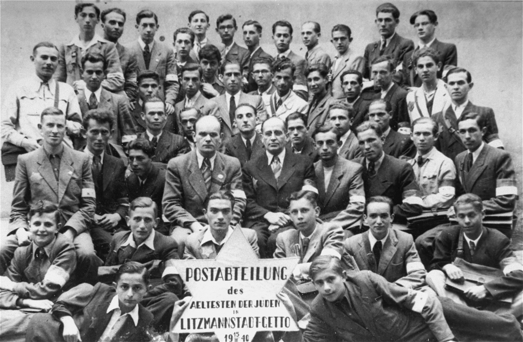 Group portrait of the employees of the Lodz ghetto post office holding a sign in the shape of a Star of David.    Among those pictured is Nachman Zonabend (top row, fifth from the left).