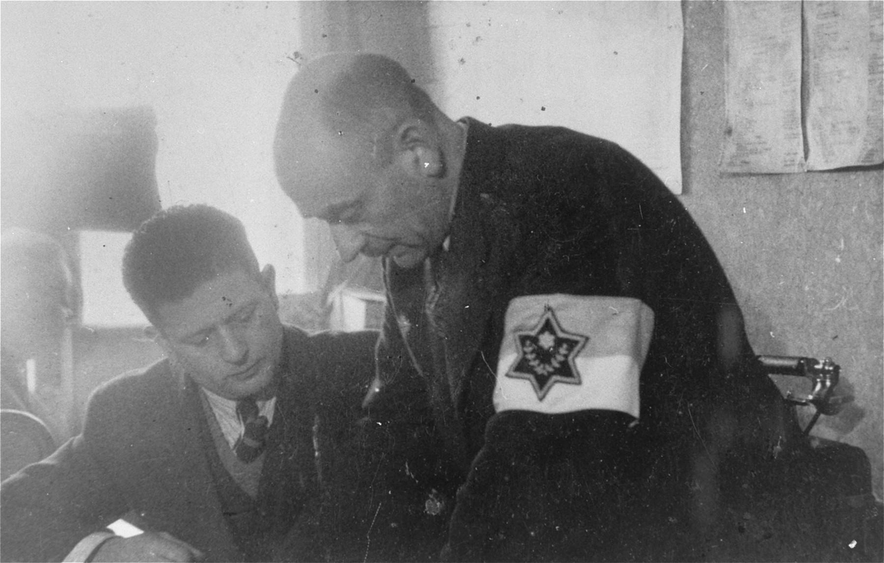 Leon Rozenblat, chief of the Lodz ghetto police (right) works with  Hermann Chimowicz in his office.