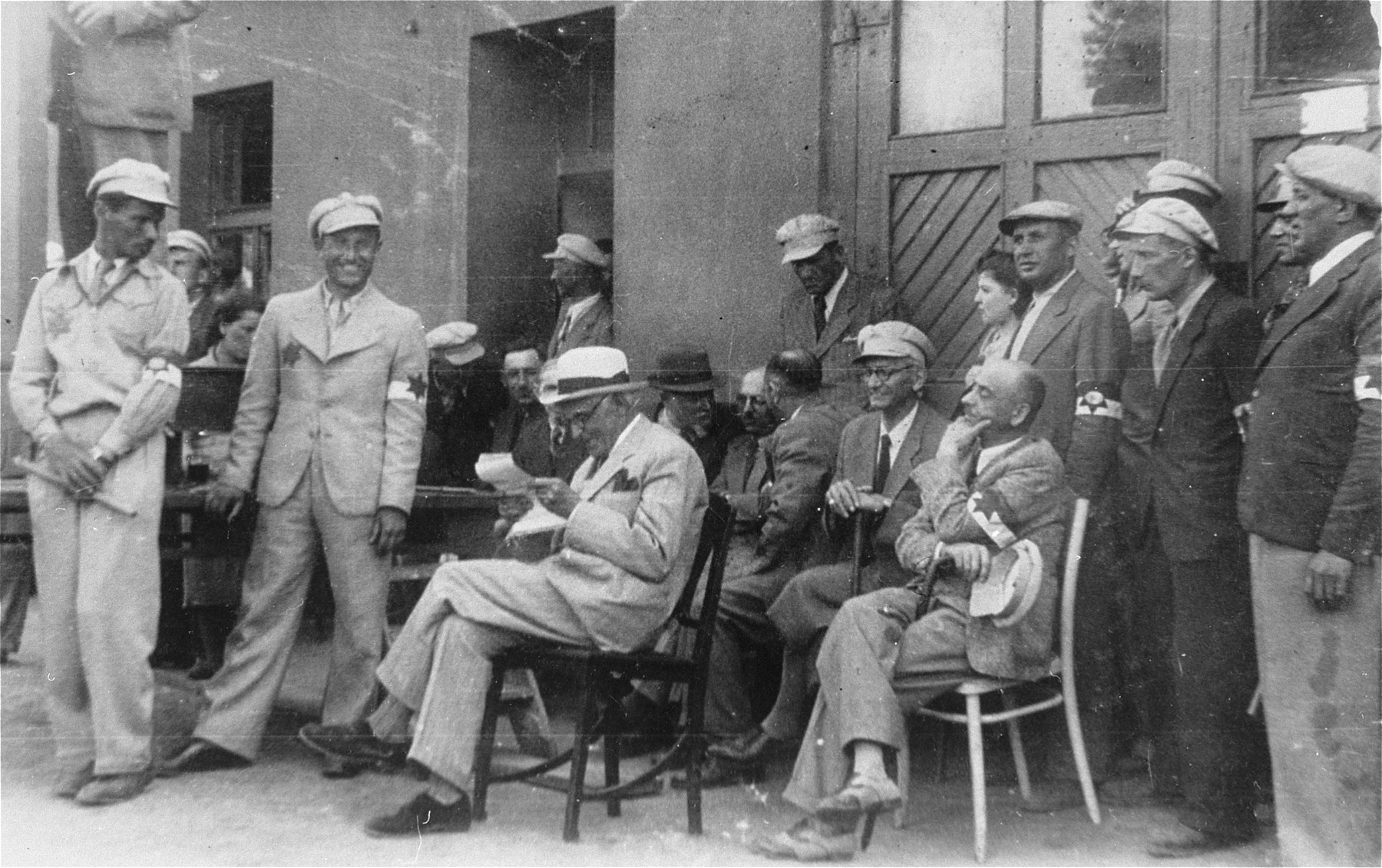 Mordechai Chaim Rumkowski (seated in the center), attends an event with members of the Jewish police and Sonderkommando.  Also pictured is Leon Rozenblat (seated at the right, holding his cap).