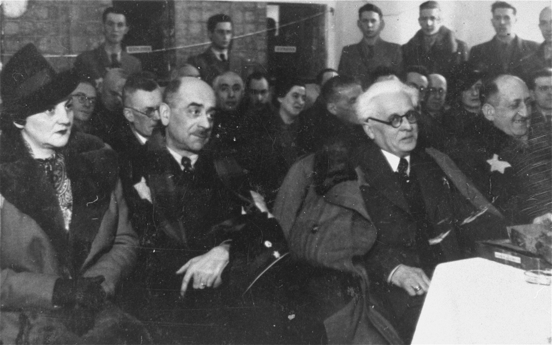 Jewish council chairman Mordechai Chaim Rumkowski (center, left), attends a ceremony in the Lodz ghetto at which he was given a presentation album.  Pictured in the front row from left to right are: Helena Rumkowska, Leon Rozenblat, Mordechai Chaim Rumkowski and Dr. Leon Szykier.
