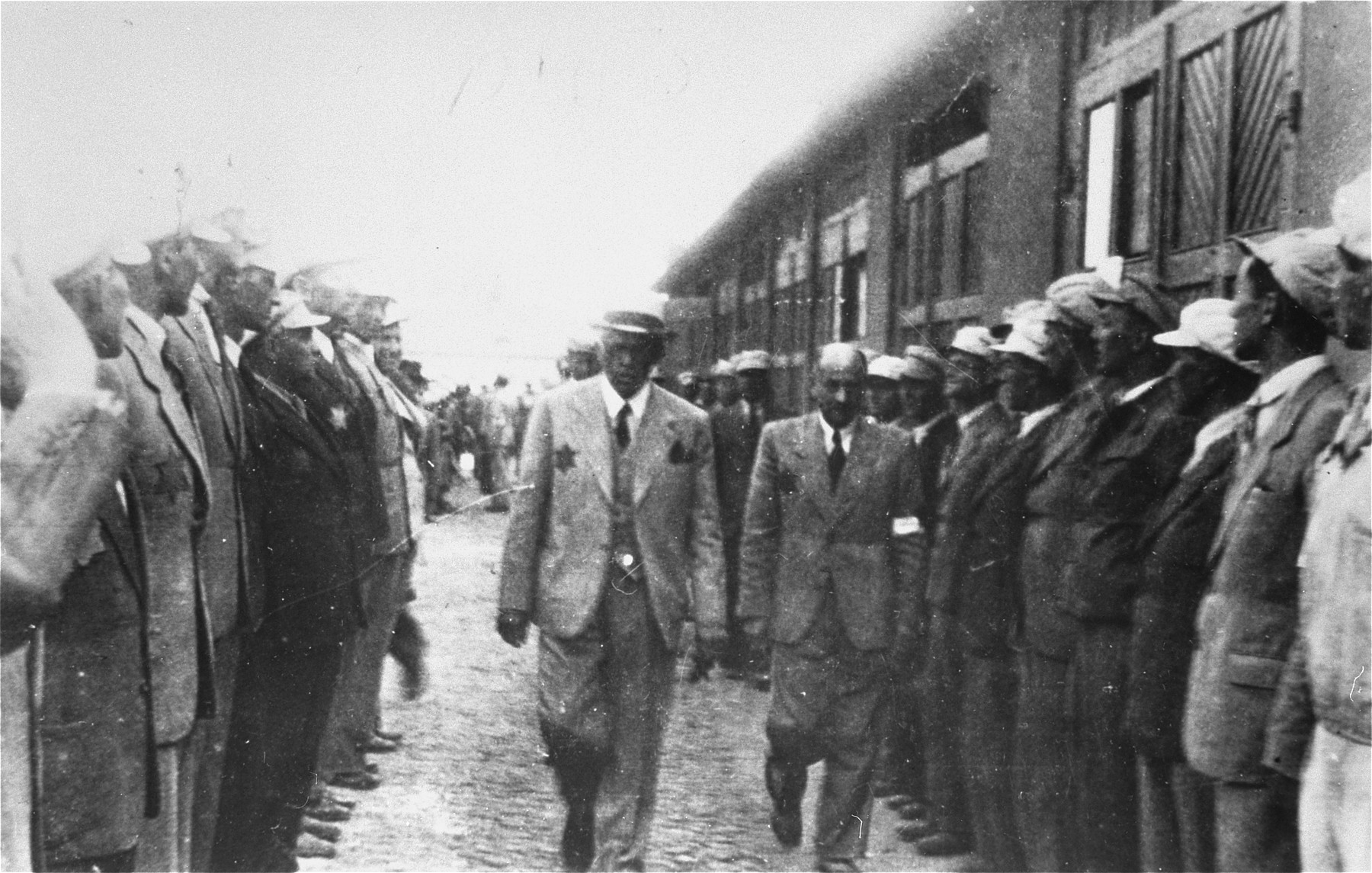 Mordechai Chaim Rumkowski and Leon Rozenblat  walk between two rows of young Jewish men in the Lodz ghetto.