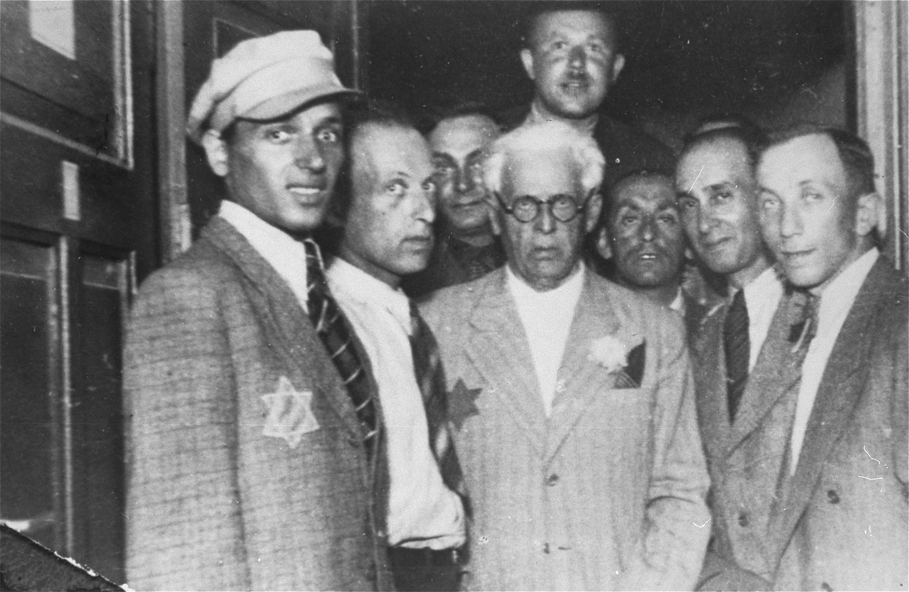 Mordechai Chaim Rumkowski, chairman of the Jewish Council (center), poses with members of the Lodz ghetto police.  Baruch Praszker is third from the right.