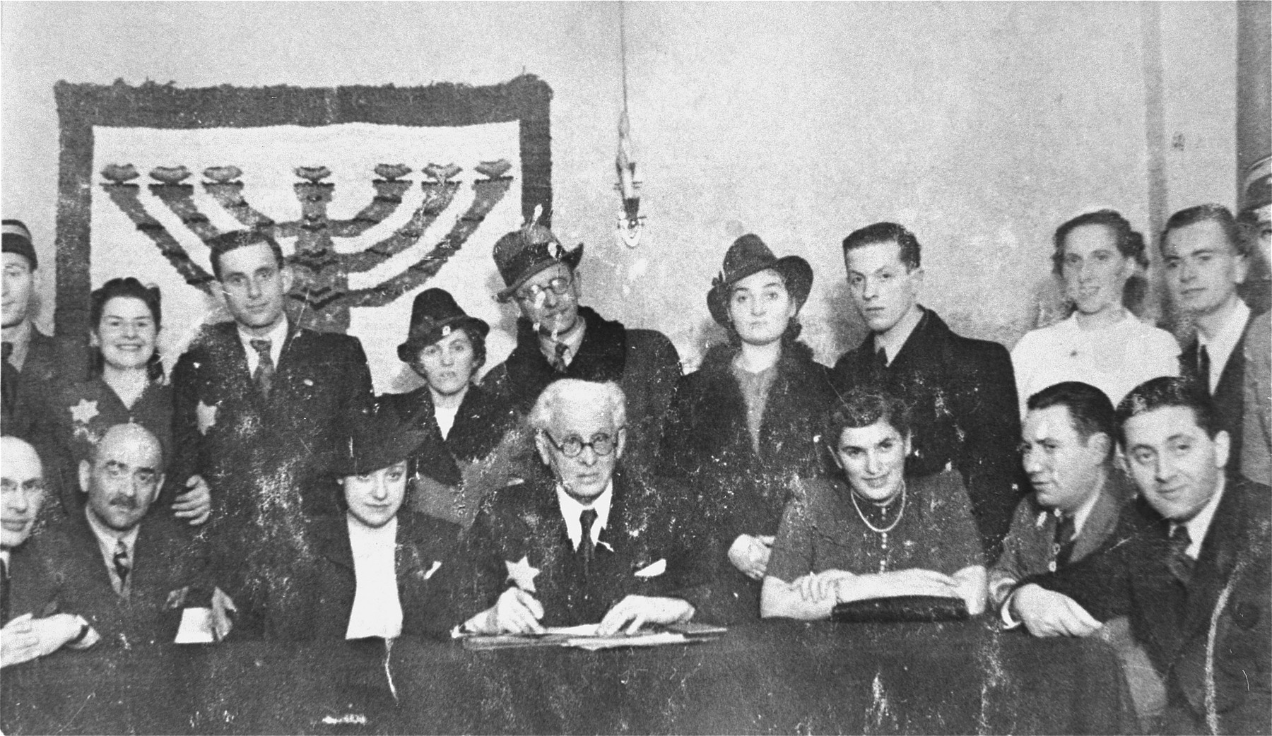 Jewish council chairman Mordechai Chaim Rumkowksi (seated in the center), poses with members of the council and four couples at a joint wedding celebration in the Lodz ghetto.  Pictured in the front row from right to left are: Aron Jakubowicz, David Gertler, Regina Jakubowicz, Mordechai Chaim Rumkowski, Dora Fuks, Leon Rosenblat and David Warszawski.  Behind them stand Robert and Sala Schick  (the bride in the white dress, on the right).