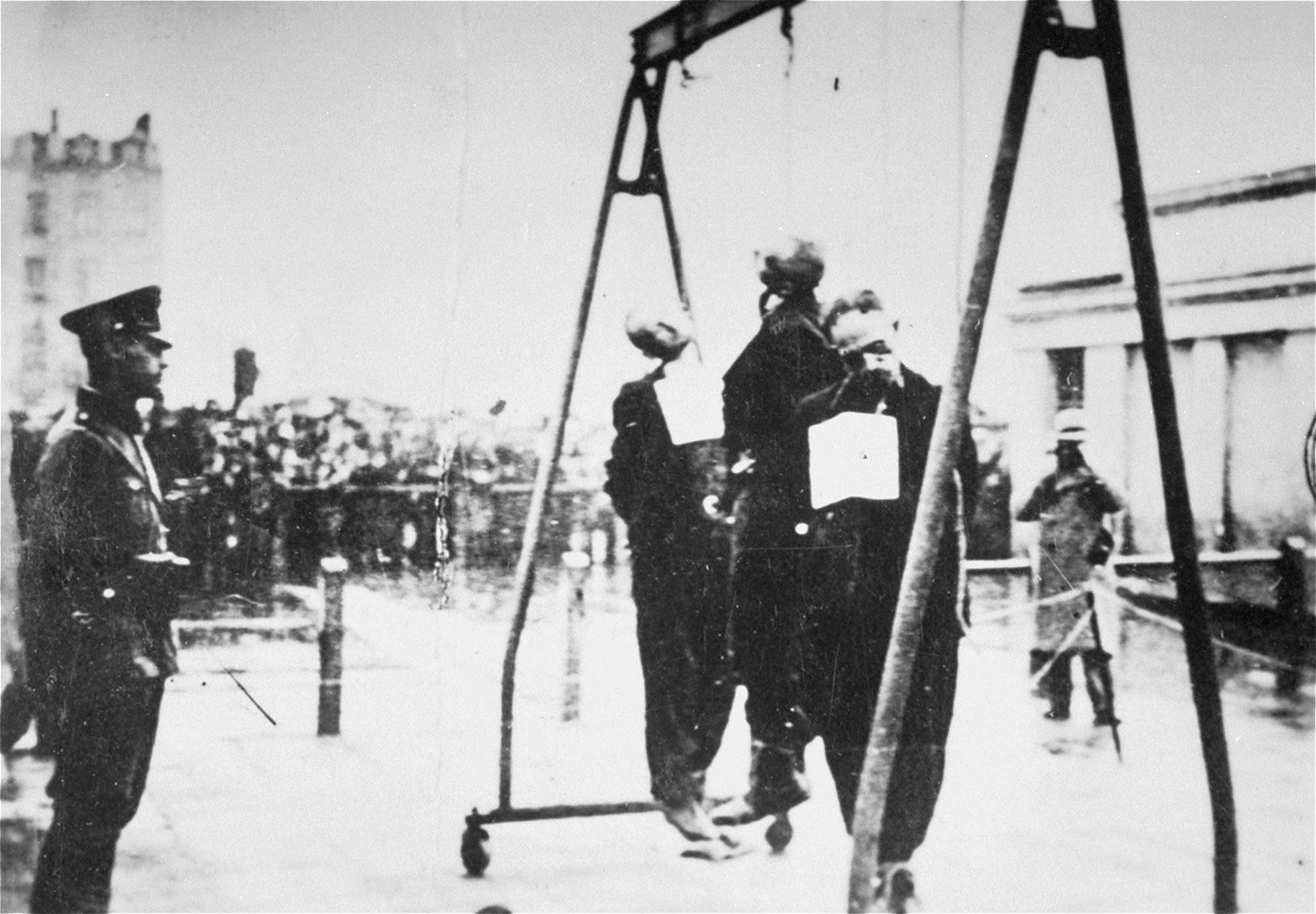 "Local residents watch as two Poles and a Jew are publicly hanged in the Baluty market square in Lodz.  The three victims wear German placards that read, ""This man was executed for being a criminal."""